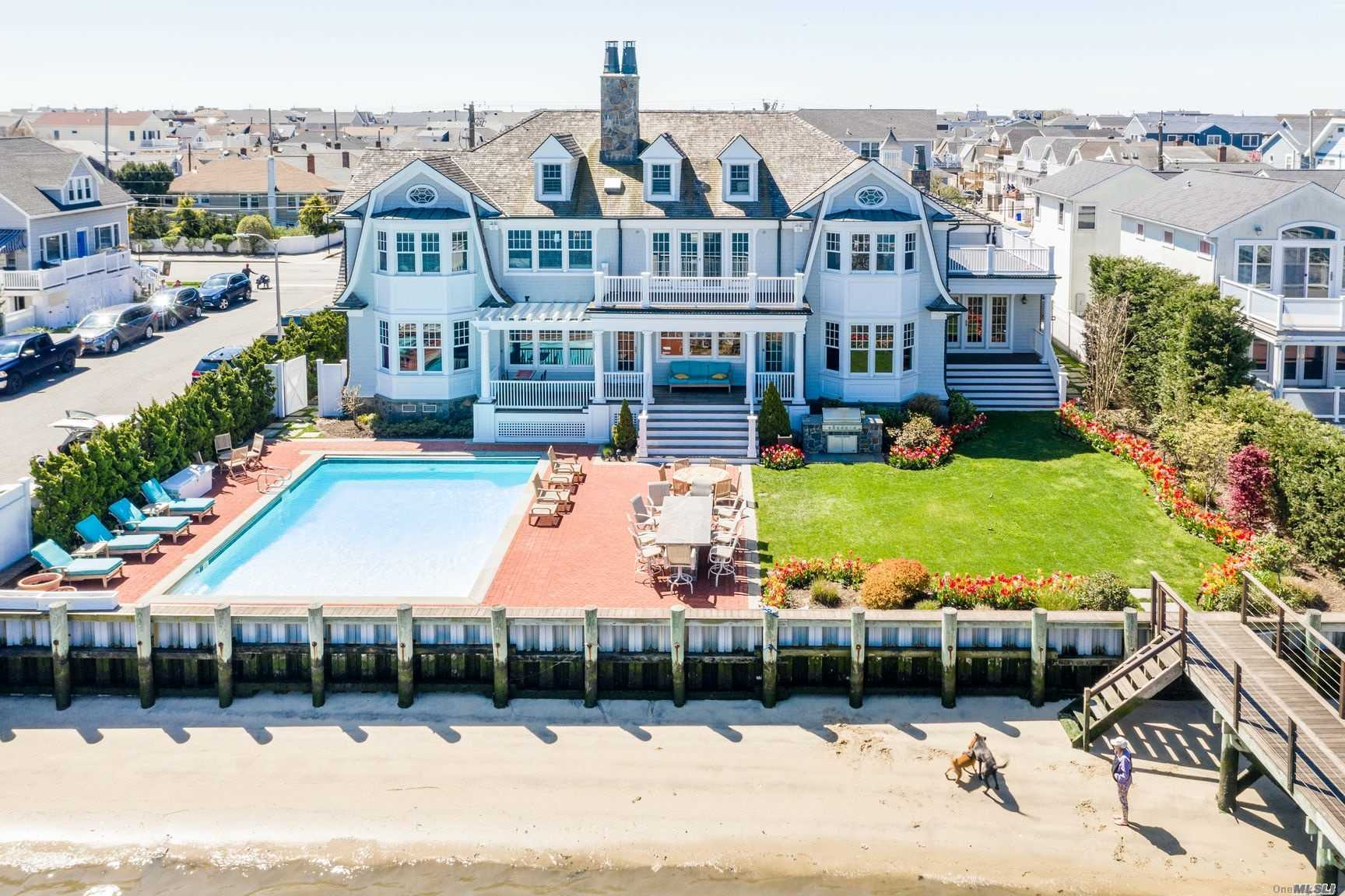 Spectacular Hamptons Like Mansion Located On Reynolds Channel With Picturesque City Skyline Views & Amazing Sunsets. 1st Flr: Grand Foyer, Sunken Living Room w/Wood Burning Stone Fireplace & Bar Area, Office, 1/2 Bath, Gourmet Chef's Kitchen w/Custom Cabinetry Marble Countertops Viking & Sub Zero Appliances & Butler's Pantry, Formal Dining Room, Family Room, Mahogany Wood Paneled Billiard Rm w/Gents Bth. Palatial Staircase to 2nd Fl: Grand Master Suite Features: Gas Fireplace, Coffered Ceiling, Large Arched Shower & Jacuzzi Tub, Double Vanity, His & Her Oversized Walk-In Closets, 4 Add'l Bdrms (2 Ensuite) & Attic Dorm Room w/Sleeping for 6. Bayfront Outdoor Living Area Features: State Of The Art Dock System w/3 Boat Lifts, IG Heated Salt Water Pool, Built In Bbq & Outdoor Bath & Shower.2 Car Garage/Parking for 10 Cars. 3D Virtual Tour Attached. Please See Fact Sheet For Full Property Details. Stunning Master Craftsmen Home w/Impeccable Attention To Detail. Must Be Seen To Be Believed!