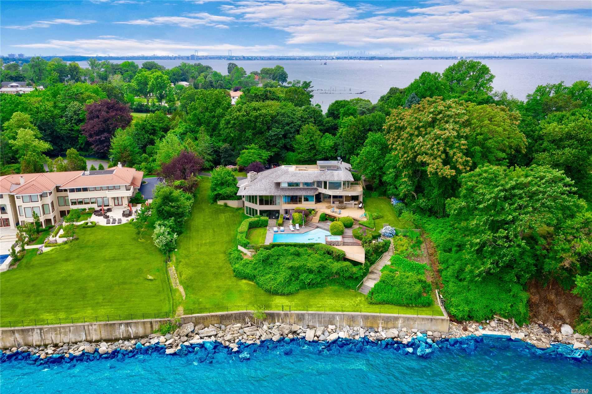 Spectacular custom built contemporary home, situated on well over an acre of waterfront property, located on one of the North Shore of Long Island's most prestigious streets, Gatsby Lane. Walls of glass provide for unobstructed of the Long Island Sound throughout every room of the home. Perfect for entertaining, the house boasts an in-ground pool overlooking the water, multiple decks and terraces, a full-sized wet bar, a billiards room, lookout point and rooftop lounge.