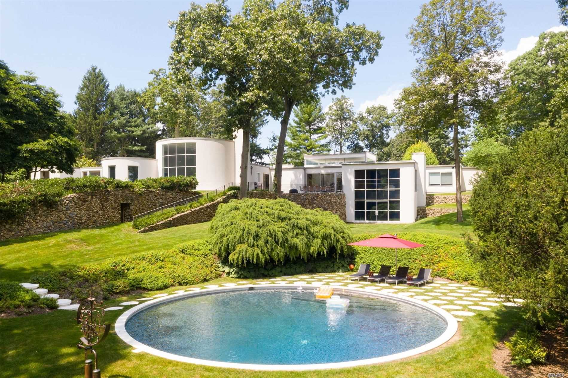 Rarely do you have the opportunity to own a masterpiece, a true work of art.This is that rare chance.Architect Wallace K. Harrison's landmarked 1930's summer house has been lovingly restored into a modern day showplace. Set on 3.6+ acres,the grounds are a private resort with a stunning circular salt water pool, new Turf Tek surface tennis court,slate patio, 8 hole mini golf, waterfall and rolling hills of lush mature landscaping. Three original circular rooms are the center design element of this mid- century modern home.The circular livingroom with original terrazzo / wood dance floor was the model for NYC's Rainbow Room. Grand rooms include : Gourmet kitchen with clerestory windows, upper /lower family rooms and library.Features include: 5 fireplaces, millwork/cabinetry throughout the house by Dune, walnut flooring and walls of glass let the outdoors in. Expanded lower/walk out level with multimedia theatre, wine cellar and gym complete this architectural showcase