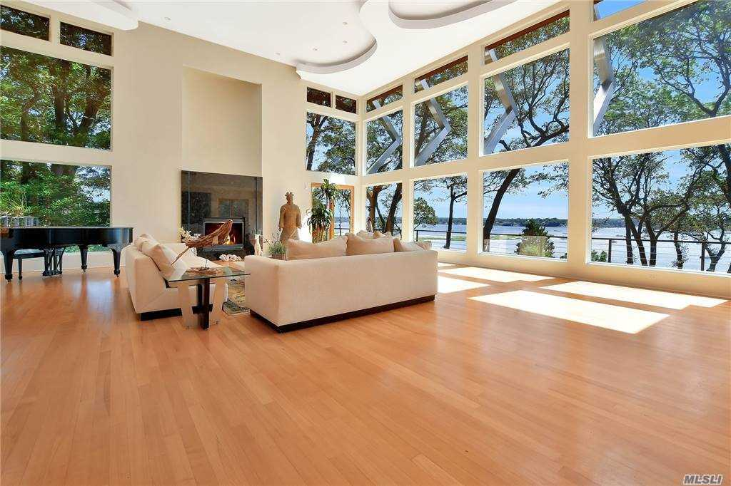 Custom designed 2006 Contemporary includes 236' of sandy beach offering the best of direct waterfront and nature with western sunsets. Private location, 3 car garage with loft, koi pond, and specimen plantings invite you into this modern 5-bedroom, 5 bath home. Unique in its design, this house is a WOW! Fall in love with the 20' walls of glass in the great room with year round unobstructed views of the bay, designer chefs kitchen with Snaidero Italian cabinetry, his and her offices, first and second floor premier bedrooms with water views, indoor spa pool with gym area, radiant heat flooring, high tech alarm system, and so much more. With more than 10 French Doors and Sliders leading from the home to the property, this house is one with nature. Twenty-two home private association includes a park like 20-acre beach, dock and mooring rights. Cold Spring Harbor Schools.