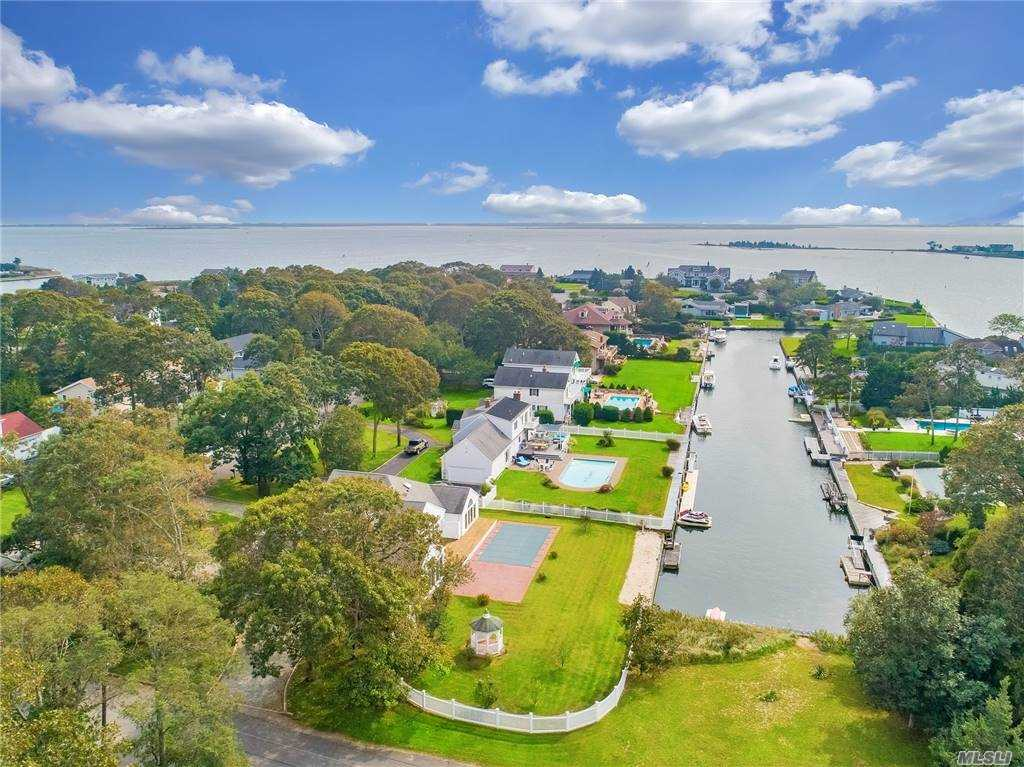 WATERFRONT, Fish, boat and swim in this  Post Modern Sprawling Ranch in desirable Old Harbor Colony with in ground pool, bulkheading and dock.  Home boasts Three bedrooms, two baths, Open concept  Living Room/Dining Room, kitchen, plus large enclosed outdoor porch for family dinners, BBQ's and social entertaining -- all while looking at your boat on the canal and relaxing.