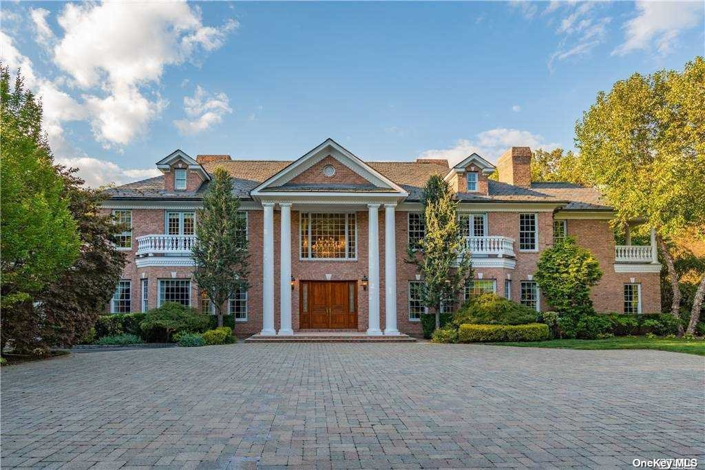 """Long private drive leads to the quintessence of """"Gold Coast"""" living! This grand magnificent 6 acre Matinecock estate is entered through two electronic gates, off two long wooded private roads. The 10,000 sf brick Georgian manor with breathtaking landscape, tennis court plus expansive multi-level stone terraces, an inground pool, two grill stations, and a charming cabana with kitchen was built in the style and grandeur of the century-old """"Golden Age"""" estates. This New Millennial home has extensive Crestron Smart House technology with remote and individual room controls for everything from heat, security, sound, lighting, the six gas fireplaces, irrigation, and more. So regal and luxurious throughout, it was the site for NBC's series, Royal Pains. Grand entrance hall, featuring twin staircases, massive moldings, gleaming inlaid marble floors, elevator, and two guest powder rooms; every room is oversized & offers stunning floors, window treatments, and moldings. View 3D Tour & Floor Plan."""