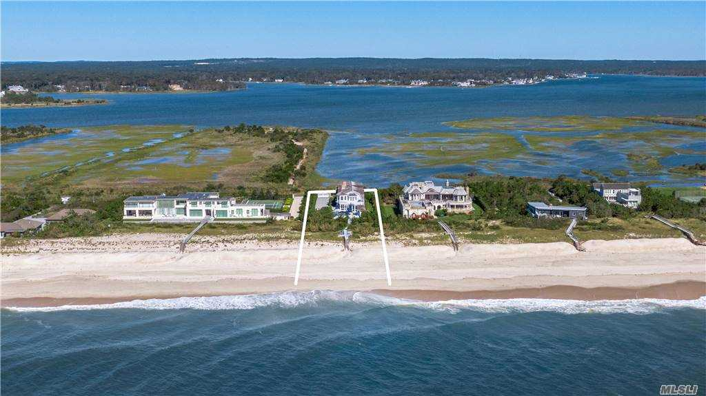 Solidly built & stunningly appointed, this custom oceanfront retreat is a study in elegance & discerning design. Sited on 1.4 protected acres directly on the Atlantic, the gated estate features an 8,038-square-foot main home, approximately 103 feet of frontage, picturesque walkway to the ocean & sandy beach, sunrise & sunset views over the water, & an expansive deck w/ heated pool & spa. The premiere property also comes w/ gorgeous views of Penniman Creek & surrounding conserved land across Dune Road. Lovingly constructed w/ an eye for detail & w/ luxury touches throughout, the main residence features six en suite bedrooms & a total of eight-full-and-one-half baths, including a primary bedroom suite w/ double closets & baths and its own oceanfront balcony; a chef's kitchen built for entertaining; & a pair of gas fireplaces. An accompanying complementary cabana-style guest cottage features a half bath, kitchen & outdoor shower.