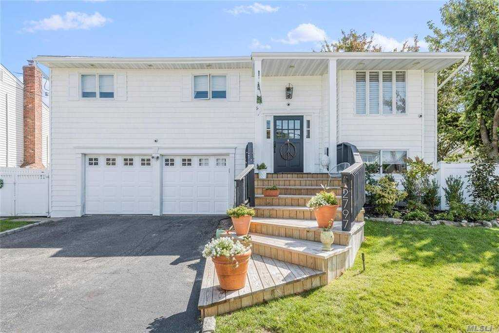 Move Right Into This Spacious Hi Ranch. Living Room w Vaulted Ceiling, Skylights, Crown Molding and Chair Rail. Beautiful Wood Floors Throughout Upper Level.  Eat-In Kitchen w Door To Large Covered Balcony. King Size Master BR Also Has Access To The Covered Balcony. Large Lower Level Den w Radiant Heated Floors, Wood Burning Fireplace and Wainscott. Whole House Water Filtration System, 200 AMP Electric.  In Addition To Two Zone Gas heat And One Zone CAC, the Two Garage Has A Split Unit Proving AC And Heat! This Is Truly A Must See!