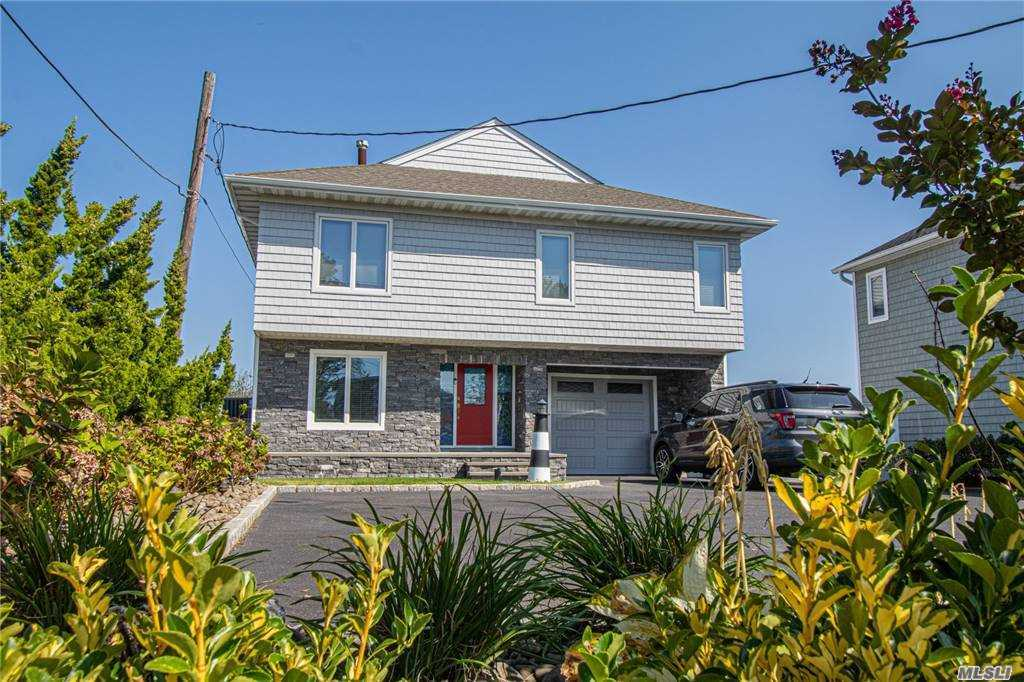 Boaters delight perfect for entertaining with spacious open kitchen, living room and dining room overseeing the beautiful wide canal. This home has 5 bedrooms and 4 baths, including one full bath in the historic boathouse. 2 Masters on each floor with master baths, one with newly updated double closets and the other with two separate walk in closets. The home Includes an elevator for first and second floors. Updated kitchen with GE Profile, entertaining space, baths, flooring and carpeting. Other highlights include, Central Vacuum, 2 new central air units, hard wired generator, 5 gas zones, new glass rails for the amazing views and fencing, 50 Feet Bulkhead, 3 finger slips, alarm system, in ground sprinklers and breathtaking Spiral staircase leading to 3rd floor loft. This is a must see!