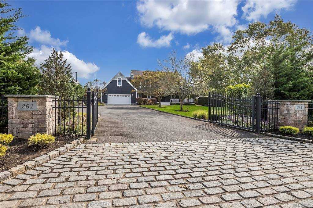 Impressive Colonial with all you could want and more! Rich Indigo cedar shake exterior, welcoming mahogany wrap around porch and grand two story foyer sets the tone for this superb home. The main level flows beautifully with the oversized great room with fireplace, formal dining room, eat in kitchen, den/office & powder room. Sliding barn doors, new wood flooring and farmhouse accents! Ascend to the second level to the grand master suite, equipped with dual walk in closets, spa-like bathroom with radiant heat, soaking tub & double vanity, vaulted ceiling & walk out balcony overlooking the lush 1 acre landscape.Three additional bedrooms, two full bathrooms & large bonus room. The homes basement is set as a home theater and recreation space with an additional full bathroom. Tons of storage and closets throughout; attached 2-car garage and long private gated driveway. The grounds boast a saltwater pool, expansive mahogany decking, outdoor shower & covered lounge area. Just exceptional!