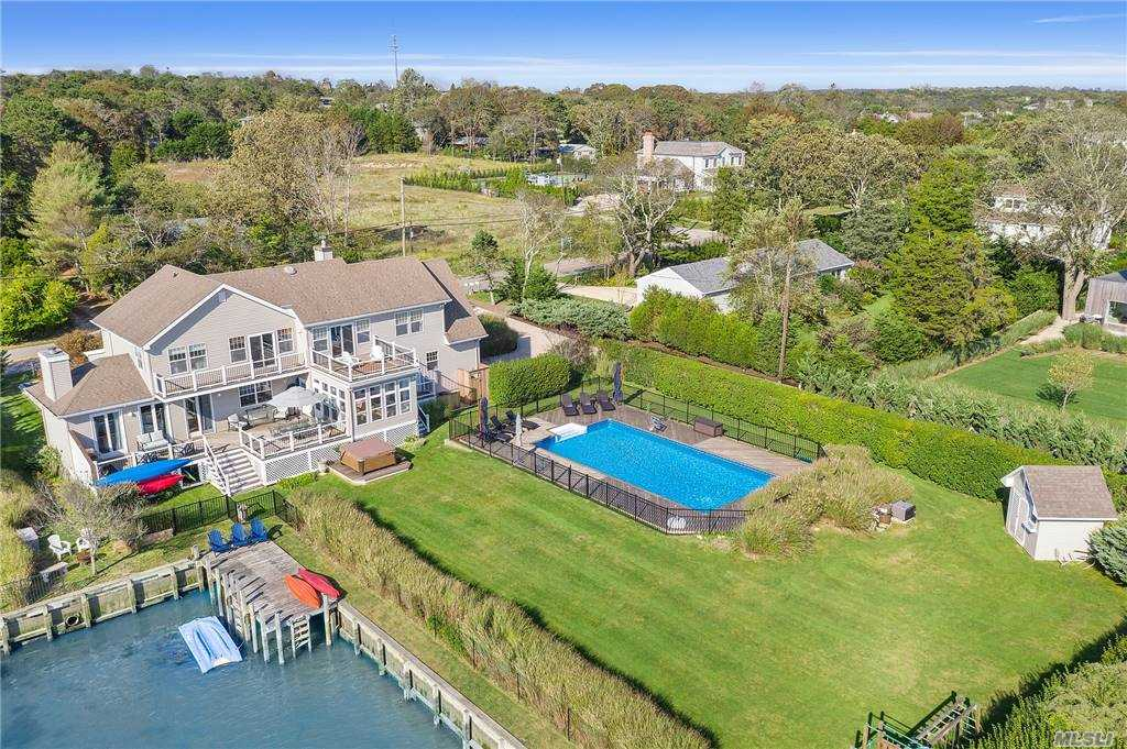 Located South of the highway overlooking Middle Pond and Shinnecock Bay, this expansive  waterfront home has it all.  The sprawling light and bright  floor plan with open kitchen, dining and great room is perfect for entertaining.  In addition to 4 Spacious bedrooms and 3 full and 1 half bath, this home has several extra rooms for your choice of home office or guest quarters. Enjoy evenings in the screened in porch while you watch the sun set over the bay.   Your private  Owner's Wing with large balcony and sitting area is the perfect getaway for some privacy.  Each guest bedroom  is individually styled with chic and beachy accessories.  Relax around the heated pool, dock your boat or take a ride on your jet skis.  Conveniently located just minutes to ocean beaches and Southampton Village center, this is a one of a kind opportunity.