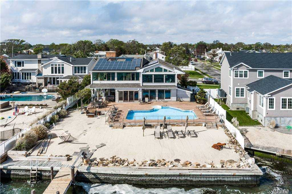"""BAYFRONT +PRIVATE BEACH + 80' BULKHEAD + 60'PIER+ HEATED 24x32 INGROUND POOL ...... You're own Vacation Resort - No need to travel! Contemporary Interior with a """"Beachy Feel"""". Luxor EIK/Center Island/Butler's Pantry & Hi-End SS Appliances.Great Rm w Brick Gas FPL & Vaulted """"Shiplap"""" Ceiling. Master Bedroom/Ensuite Bath/WIC & Gym/Steam Shower overl.Upper Level Sitting Room or Office, Floating Staircase, 8 Skylights,  Interior & Exterior Surround Sound, Zebra HW flooring, Walls of Glass & Mirrors offer Panormanic Views of the Great South Bay. Exterior boasts a Circular Paver Driveway & 2car Garage plus an indescribable Backyard! You have to see it to believe it...."""
