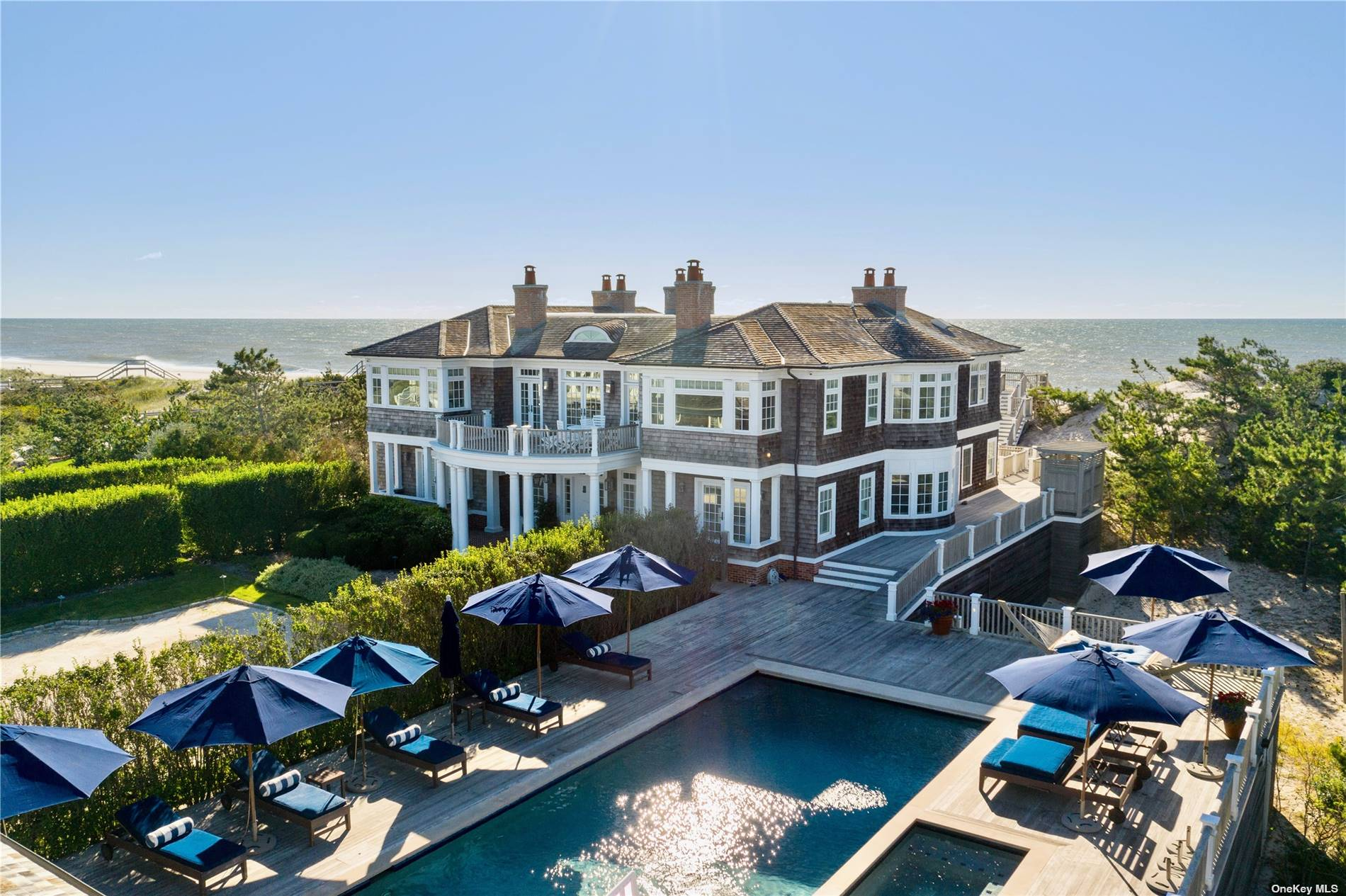 Extraordinary panoramic ocean to bay views. Over 2 acres with 167 feet of ocean frontage. This impressive beach front estate consists of a 7,000 sq. ft. main house, 3-bedroom guest cottage and pool/entertainment house. This traditional shingle-style home, designed by Stuart Disston, includes many unique features. The main floor features a large living room with fireplace with doors leading to a deck overlooking the ocean, a family room, formal dining room, chef's kitchen with views of Shinnecock Bay, breakfast room, library, and sumptuous master suite. The lower floor consists of six bedroom suites, movie theater and play room. The guest cottage has three bedrooms, kitchen/living room. The pool house features a large entertainment room, cooking facility, gym and two baths . A large swimming pool with spa and a har-tru tennis court await your pleasure. Impressive by any standard, this significant beachfront property is now available.