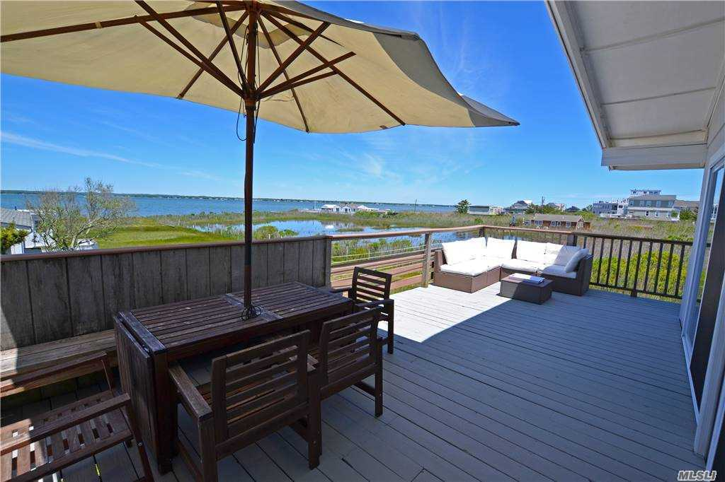 Own one of the last beach bungalows in the Dunes on a quiet lot set back from a Dune Rd with protected views of Moriches Bay. Updated and well-maintained. Expansive deck with room for a pool. Take advantage of all beach living has to offer. Ocean beach access directly across the street and deeded ROW to Bay with boat mooring rights. Great rental potential. Renderings for rebuild available.