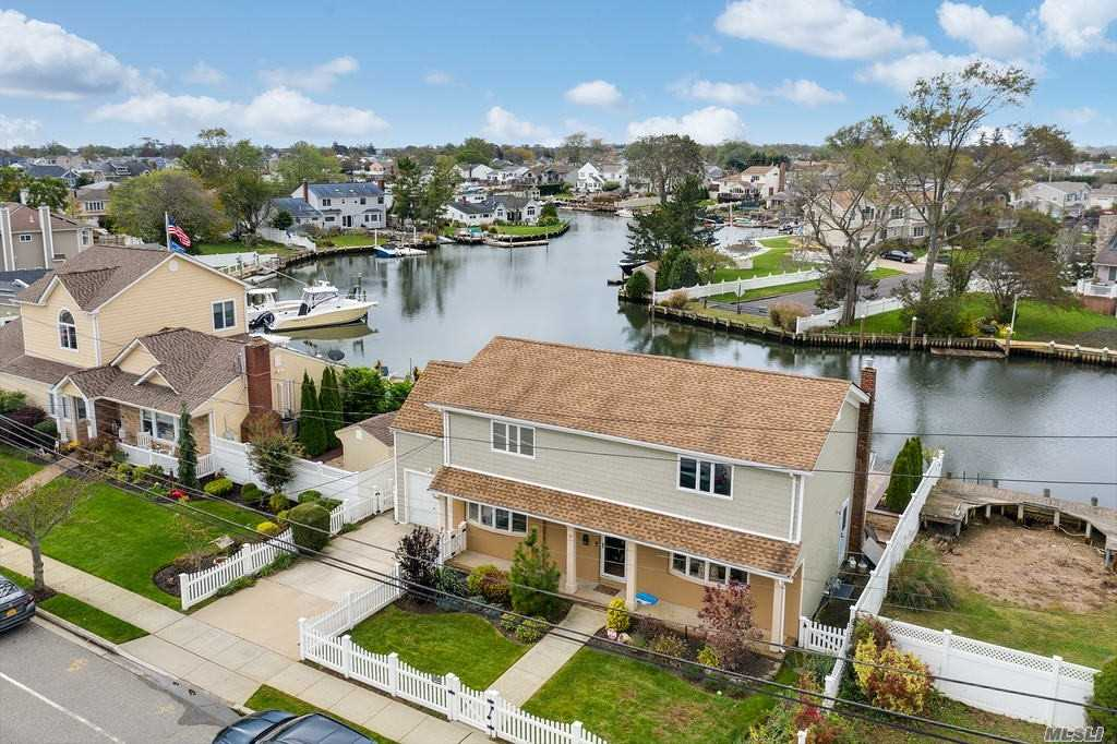 Calling ALL BOATERS! Located On The Massapequa River Just Minutes To The Bay! This Colonial Style Home Of Almost 2700 SqFt. Truly One-Of-A Kind Spacious & Pristine Waterfront Property On Large Canal W/ 60 FT Of Bulkhead & Room For Jetski Dock. This Home Was Completely Renovated, Features Andersen Windows, Cac, Oak Floors, Recessed Lighting, Crown & Picture-Frame Moldings, E-I-K Chef's Kitchen Has Been Totally Updated, SS Appls, Tile Backsplash, Ceramic Tile Floor, Center-Island, Updated EVERYTHING, Formal Dining Rm, Living Rm, Glass Andersen Sliders To Paver Porch/Patio/Dock, Brand New Bulkhead, 2nd Floor Master + His & Hers Closets. Garage With Finished Loft Is Being Used As Living Space, But Can Be Converted Back. New Boiler, New AC Unit, Taxes Never Grieved.