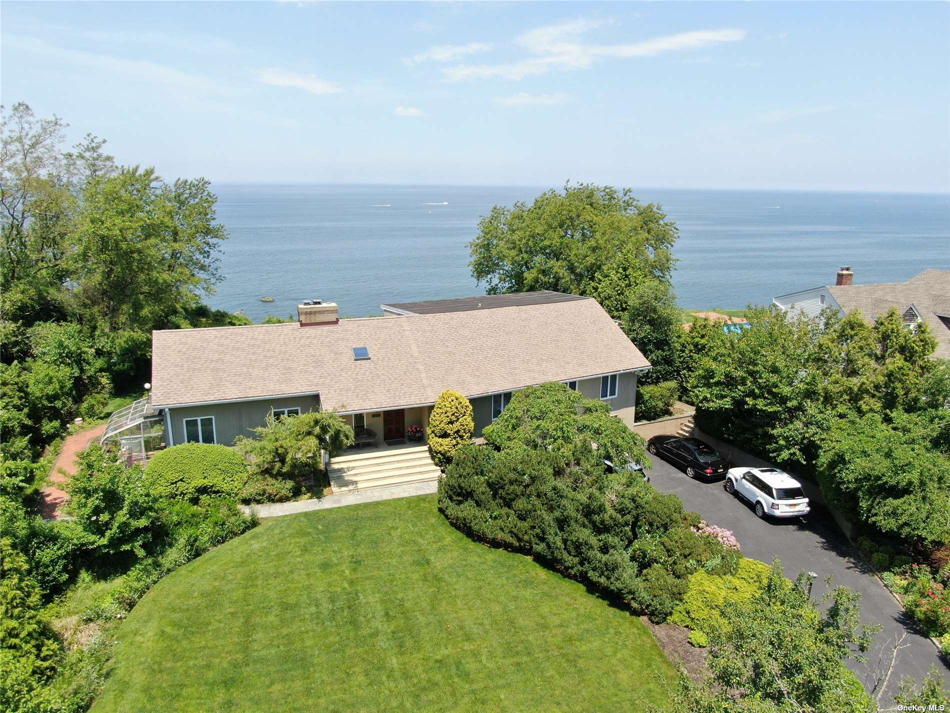 A seaside oasis. This gorgeous home has breath taking views of Long Island Sound. Plenty of windows throughout engulf the home in natural light & showcase the beautiful views.  Vaulted, wood beamed ceilings, a floor to ceiling brick fireplace & large archways in the living room give the home a grand feel. The large eat-in-kitchen has a continuation of the beamed ceilings, dark wood cabinets, Iron stone flooring, & SS appliances providing a Mediterranean feel.  Leading from the living space to the rear deck is an expansive IG Pool & beach. Wake up to a beautiful view in your spacious master bedroom featuring two WIKs & private en-suite. This home was expanded w/ a 2nd story guests quarters or home office complete w/ a living room, kitchen, bedroom & bath allows you to keep your guests close while both enjoying your privacy. Private beach rights stairs border the property to the west. A 22KW generator & a new sea bulkhead in 2020,  bluff is fully intact securing this home for many years.