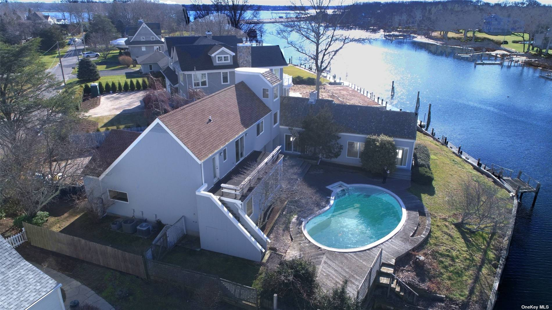 Mid-Century home on Gull Pond with access to Peconic Bay. Property features, bulkhead, dock, and waterside pool on coveted Snug Harbor in Greenport. Spacious and bright with water views from nearly every room. Wood burning fireplace, large, vaulted living room, sunroom, 2nd floor water side balcony, 3rd floor office/observatory, 2-bay garage, full basement with walkout workshop & bilco. 30' dock with 6' draft at low tide can accommodate large boat.