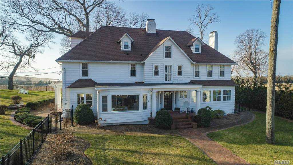 """Tranquility is only one of many words to describe this one of a kind 5bd, 3.5 bath colonial sitting on 1.5 acres of waterfront property. Set back at the end of a 100 Ft. driveway, sits your own private oasis.  Enjoy year round sunsets from your sprawling sunroom or boat house. The 110ft private bulkhead is perfect for a boat or kayak launch. This home offers many """"smart"""" features, a water filtration system, beautiful moldings as well as an updated kitchen with granite countertops, a full basement partially finished with outside entrance, updated bathrooms, floors and windows as well as a  large attic with cathedral ceilings and a separate 100 amp electric panel. Property also has a potting shed and seperate 1 bedroom 1 bath cottage with a seperate meter."""
