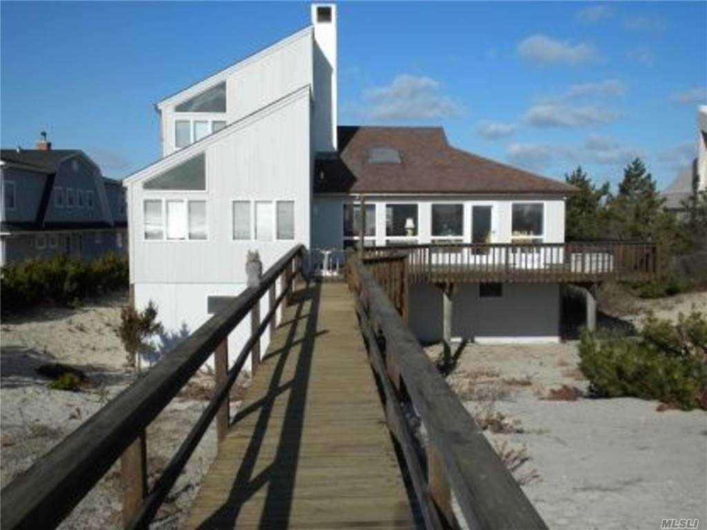 Quintessential 5BR, 3BA beach house.  Amazing ocean & bay views abound.  An open living room with wood burning fireplace has access to a broad deck & wooden path to the ocean.  There is an attached 2 car garage.  There is 85 feet of ocean frontage & the wide beach is jetty protected.  Deeded right of way to the bay is directly across Dune Road.  With almost a full acre in a premiere location there is ample room to build your spectacular dream house with a pool.  Minutes to Main Street's restaurants, shopping and Performing Arts Center.  *Taxes listed are just the Town of Southampton. VILLAGE TAXES ARE TO BE DETERMINED*