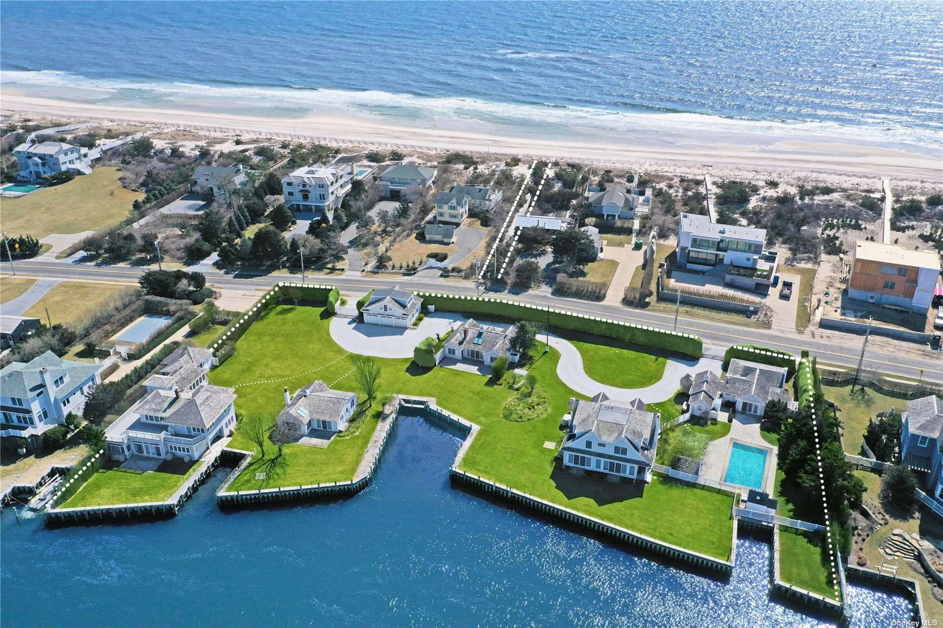 A spectacular Bayfront opportunity now exists in Quogue. This one of a kind property consists of 2 Main residences and 3 beach cottages with a total of 17 bedrooms and 11.5 baths. There is a 3 car detached garage with a gym above it. The property features a generator, sprinklers, heated saltwater pool, 500' bulkhead, 3 boat slips with water and electricity, and deeded ocean access across the street. Subdivide and build two mansions in their own parcel or enjoy the existing perfect waterfront compound. What more could you want?