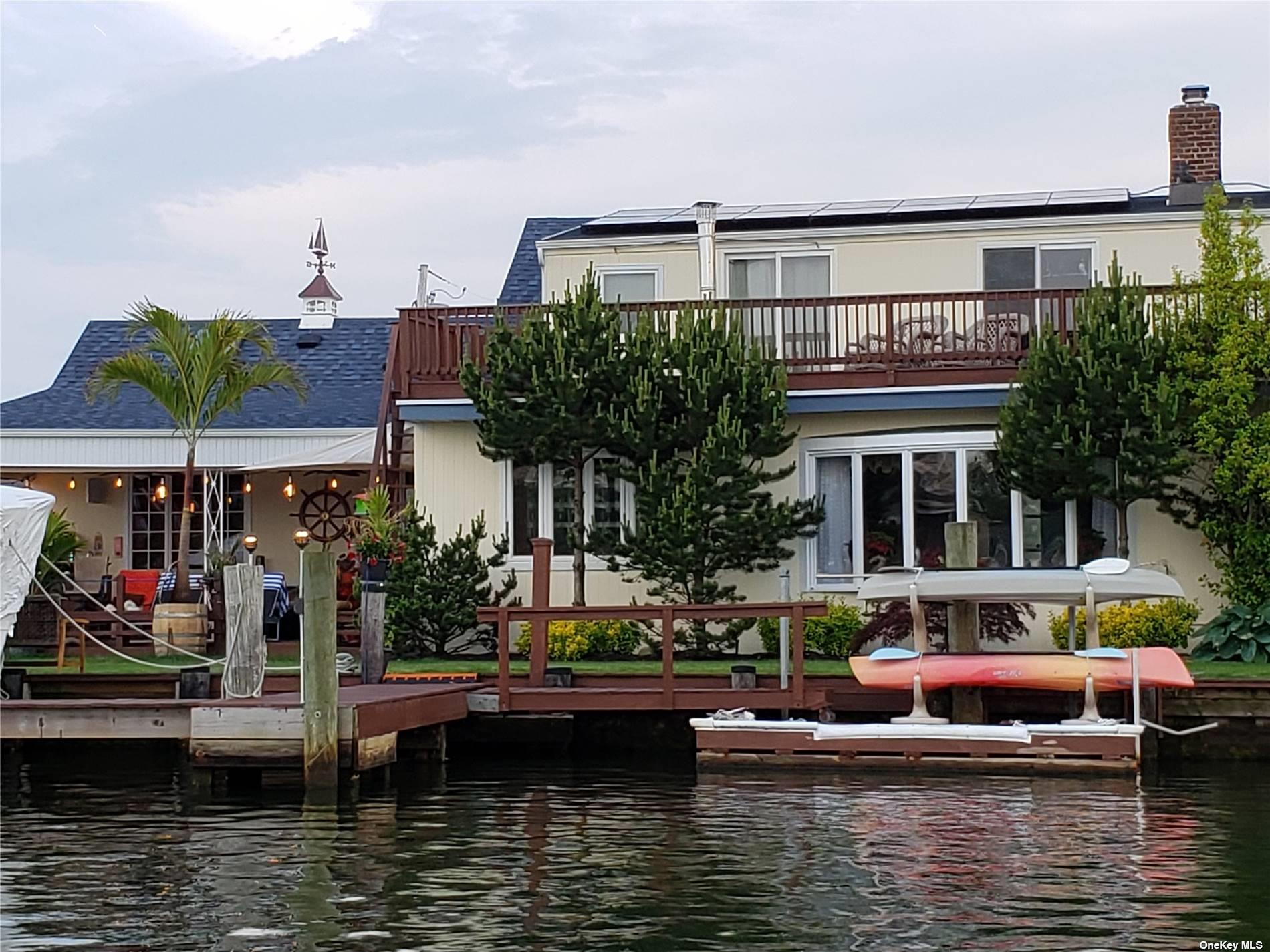 Boaters/Entertainers/Family Paradise! Oversized lot with 200+ foot bulkhead on a wide river minutes to open bay on a cul-de-sac!  Waterfront includes 300 feet of lighted boardwalk and L-shaped pier with water/electric towers, launch ramp, lift and floating dock with kayak storage/launch.  Water views from 8 rooms and 2 oversized attics with skylights.  Upper deck accessible from 3 bedrooms and lower patio that includes kitchen with natural gas stove, BBQ, fridge and hot/cold water.  This estate includes 16x24 indoor heated pool with computerized salt system and new transparent roof.  The house boasts brand new Thermador kitchen, 4 new full bathrooms, video/alarm system and 2 fireplaces.  This fully fenced property has circular driveway and a separate road leading to a hidden 2 car garage with side space for RV/boats, 12 zone sprinklers and WiFi enabled 3 zone lights system.  It also includes brand new roof with solar powered electric supply and automated battery back-up system.