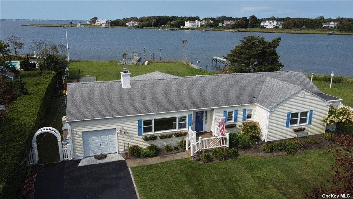 With Moriches Bay as your backdrop, enjoy sunrises and sunsets from this beautiful waterfront property offering a generously sized and gracious living room with fireplace and dining room both perfectly designed for entertaining. This one level residence offers master suite, two guest bedrooms and bath, flagstone patio overlooking the bay and a one car garage. Sited on over a half acre, the property has over 90' of bulkhead complete with a 50' dock.