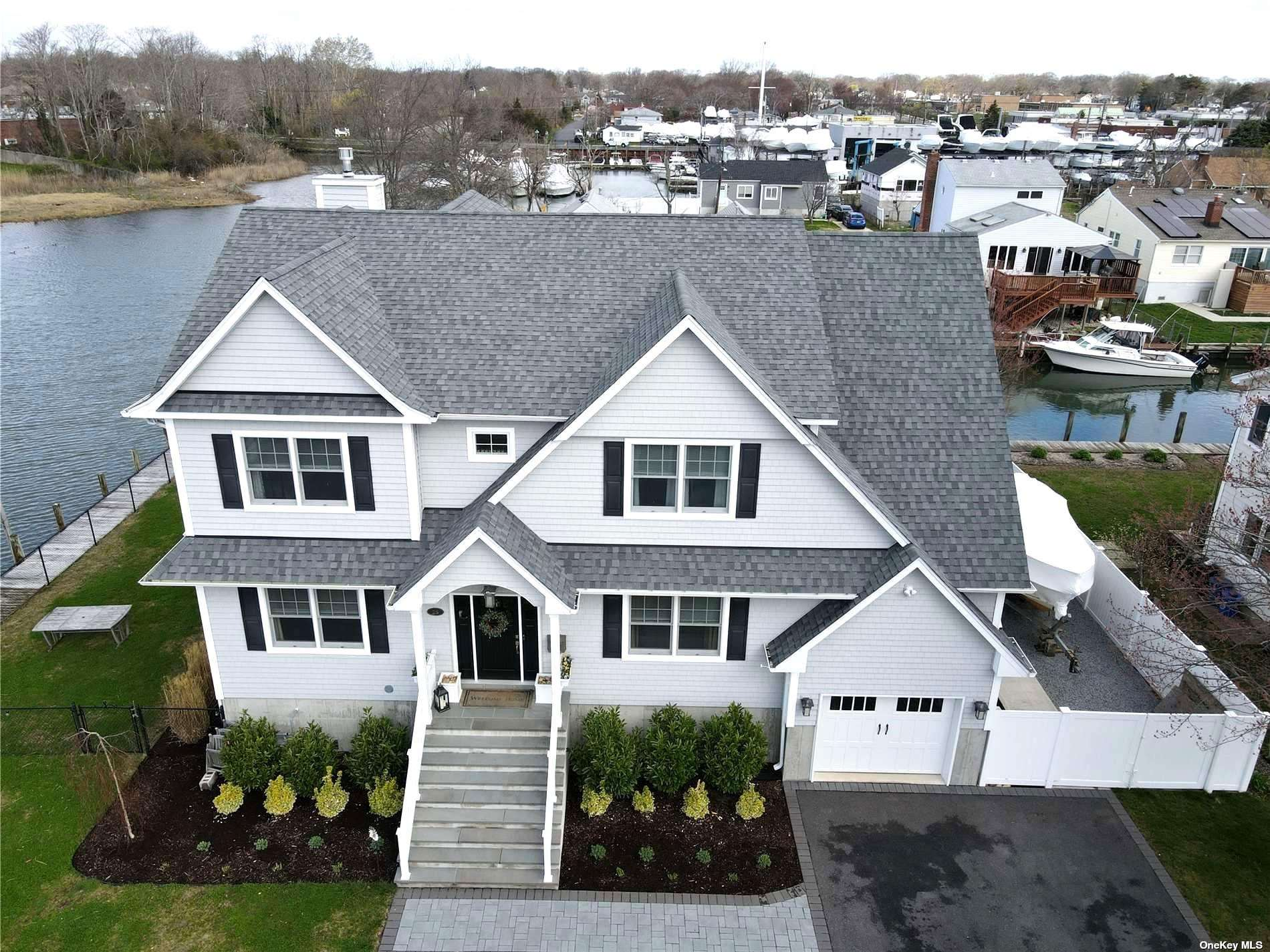 Gorgeous custom built (completed in 2017) 3 bed 2.5 bath colonial on the end of a dead end street in Amity Harbor with 200' feet of bulkheading on the canal.  Beautiful waterfront views from every room, open and airy floor plan with 9 foot ceilings, fenced yard plus garage, loads of storage in attic and dry crawl and super low flood insurance because of high elevation. Beautiful custom details include open eat in kitchen with birch cabinets, center island and quartz countertops, sliding barn doors in family room, double sided gas fireplace, radiant heated floors, unfinished 4th bedroom, exterior soffit lighting and central air to name a few.  Just in time for  summer boating season- must see home!