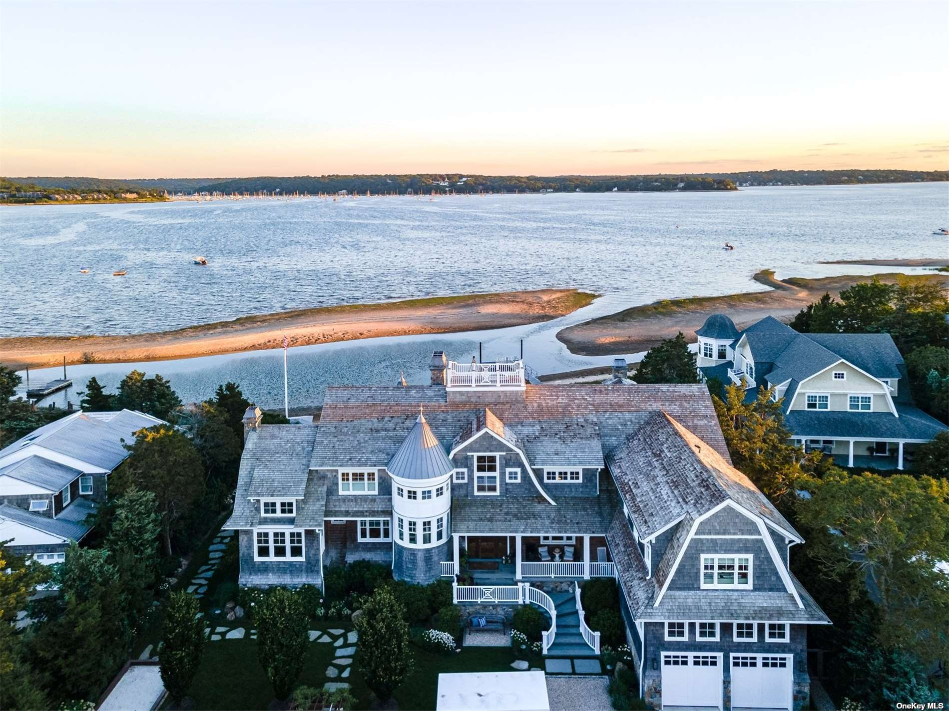 """Exquisite Hamptons-Style Gambrel Home newly built in 2017, situated on a double lot in Asharoken facing Northport Bay totaling 5.44 acres. Approx. 150' of Bay Frontage with Private Beach and Permitted Dock. Outdoor Full Kitchen utilizing Natural Gas. Main Home Featuring 4 Bedrooms, 4 Full Baths, 2 Half Baths, Home Gym, Two (2) 110 Bottle Wine Cooled Storage, Formal Living, Billiards Room, Home Office Study, as well as a Detached 2 Car Garage with Guest Quarters and Full Bath Above. Enjoy a Cigar or some relaxation in the Gentleman's Lounge located in the finished attic with a roof hatch leading to a roof deck with sweeping views spanning Long Island Sound, Northport Bay, and Asharoken. Plenty of storage in the unfinished crawlspace with 7.5' ceilings. Outdoor Living features a Full Kitchen w/Automatic Retracting Covered Pergola & Pizza Oven, Nat. Gas Fire Pit, Grass Tennis Court. Exclusions include """"Murray"""" Outdoor Statue leading to Dock and Murano Lighting Pendants in Master Bedroom."""