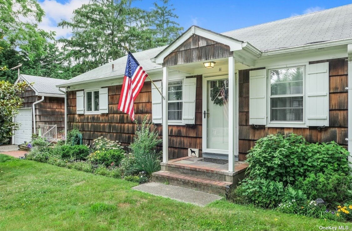 Arguably one of the most desirable locations in Bellport Village! Your home is on a very short dead end Lane that features a huge backyard that's encased for wonderful seclusion from the outside world by large evergreen specimens- yet you're just a short stroll to town. A town, village that was named as one of the happiest seaside towns in ALL OF AMERICA by Coastal Living Magazine! It's the rare mix of incredible seclusion, peace and quiet, coupled with the fact that you're just a hop, skip, and a jump to our fine restaurants, shops, [residents only] ocean beach on famous Fire Island! Other amenities include 3 bay beaches, 18 hole golf course and tennis courts that makes this location so very desirable! Full basement with interior and exterior access. Expandable attic, large attached garage with tall ceiling and rafters with door to expansive backyard. Hardwood  floors, charming country kitchen, adorable porch, breakfast room, two good sized bedrooms, full bath and lovely living room.