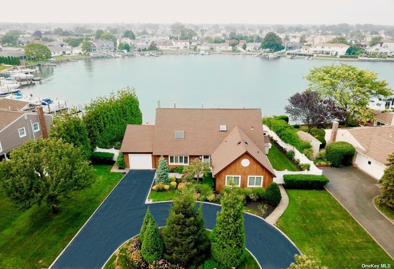 Stunning 2,900 Sq Ft, 4 Bd 3 Bth Contemporary Waterfront Set On A Spectacular 55Ft Deep Lagoon In Copiague Harbor. Enjoy breathtaking sunrises on a multi level trex deck with 94 Ft of Navy BKHD, 35x12 Ft floating dock and 35x4 fixed pier with swim ladder. Entering the home, you find an open floor plan, VLT ceilings, a sunken LVR rm with bamboo floors. Architect dsg kit/w custom wood mode cabinets, qtz top and s.s appliances. Formal DIN rm with beautiful water views. 1st fl features 3 Bd, 2 Bth w/guest wing. Open staircase takes you to the 2nd floors fabulous sky loft lounge, VLT ceilings overlooking the 1st floor. Built in wet bar, stone fireplace, bamboo fl, and large glass windows/doors overlooking the entire lagoon. The owners suite features a spa bath, 2 clo, bamboo flooring, glass doors overlooking the water. 2nd story trex balcony with s.s wire rails. Centrally located, only 60 min to NYC and the Hamptons. Beach, boating, kayaking & paddling are just few of the great amenities