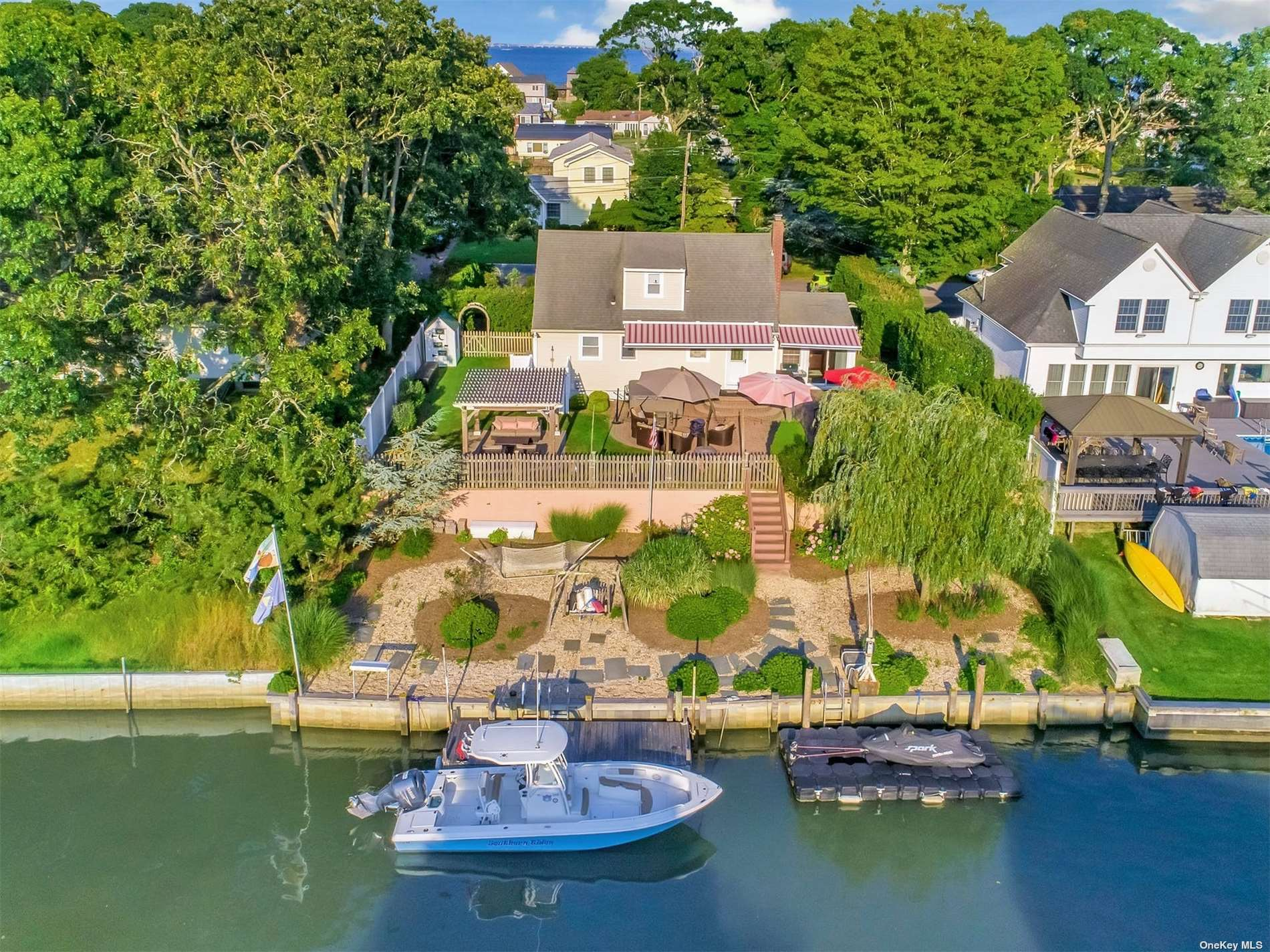 Located on Shinnecock Bay tucked away in the southern part of East Quogue is this private community. With it's five canals, private sandy bay beach and play ground, this certainly has the amenities that can suit any buyer's needs. This home offers a great outdoor entertaining space with a large paver patio to lounge upon with backyard space for lawn games. Jump on your boat or jetski located on the spacious floating dock behind the home and after a long day on the water, freshen up in the enclosed outdoor shower. With an easy commute from NYC and nearby to extraordinary waterfront restaurants and ocean beaches, only minutes away by boat or car, this is an exciting opportunity to own a waterfront home that affords you the lifestyle you can share with family and friends. This is the Hampton's lifestyle that dreams are made of, come see for yourself!