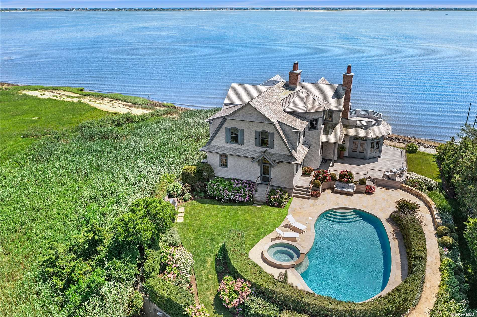 First Offering of This Bayfront Beauty!  Custom designed by renowned architect Stuart Disston and constructed by Sea Level in 2011, this Nantucket style shingled home on Moriches Bay is a paragon of exceptional craftsmanship and the finest attention to detail.  The deep flag lot setting and adjacent protected land afford privacy while the open bay offers a panorama of water views across to Dune Road.  Expansive mahogany decking, heated gunite pool and spa, outdoor kitchen, and private dock - having it all never looked so good!  *Exclusions: Dining Room Chandelier, Living Room Drapes, Primary Bedroom Drapes