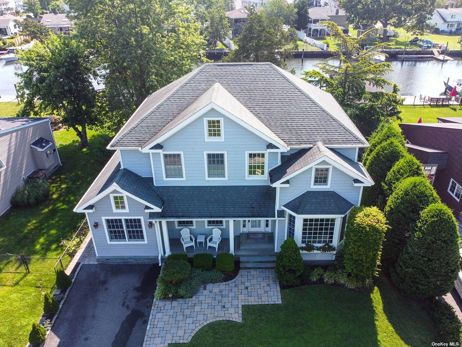 This breathtaking Hampton styled waterfront colonial in Nassau Shores has so much attention to detail it will not disappoint!  The bright soaring entry brings you to French doors which open to the formal living room.  All of the doors are surrounded by beautiful molding and custom trim work and transom windows which continue the bright and airy feel throughout the home. Beautiful hardwood floors grace the entire home.  The formal dining room features custom built ins and the gas fireplace is flanked on either side by custom shelving.  The kitchen is built for entertainment with a dual oven, separate warming drawer, beautiful silestone countertops and sliders that open to the backyard.  While of course the master has a gorgeous ensuite as well as its own walk in closet it also has its own private balcony where you can take in beautiful waterfront views.  With bluestone accents on the exterior of the home and 60 feet of bulkhead and a pier this charming colonial won't last!