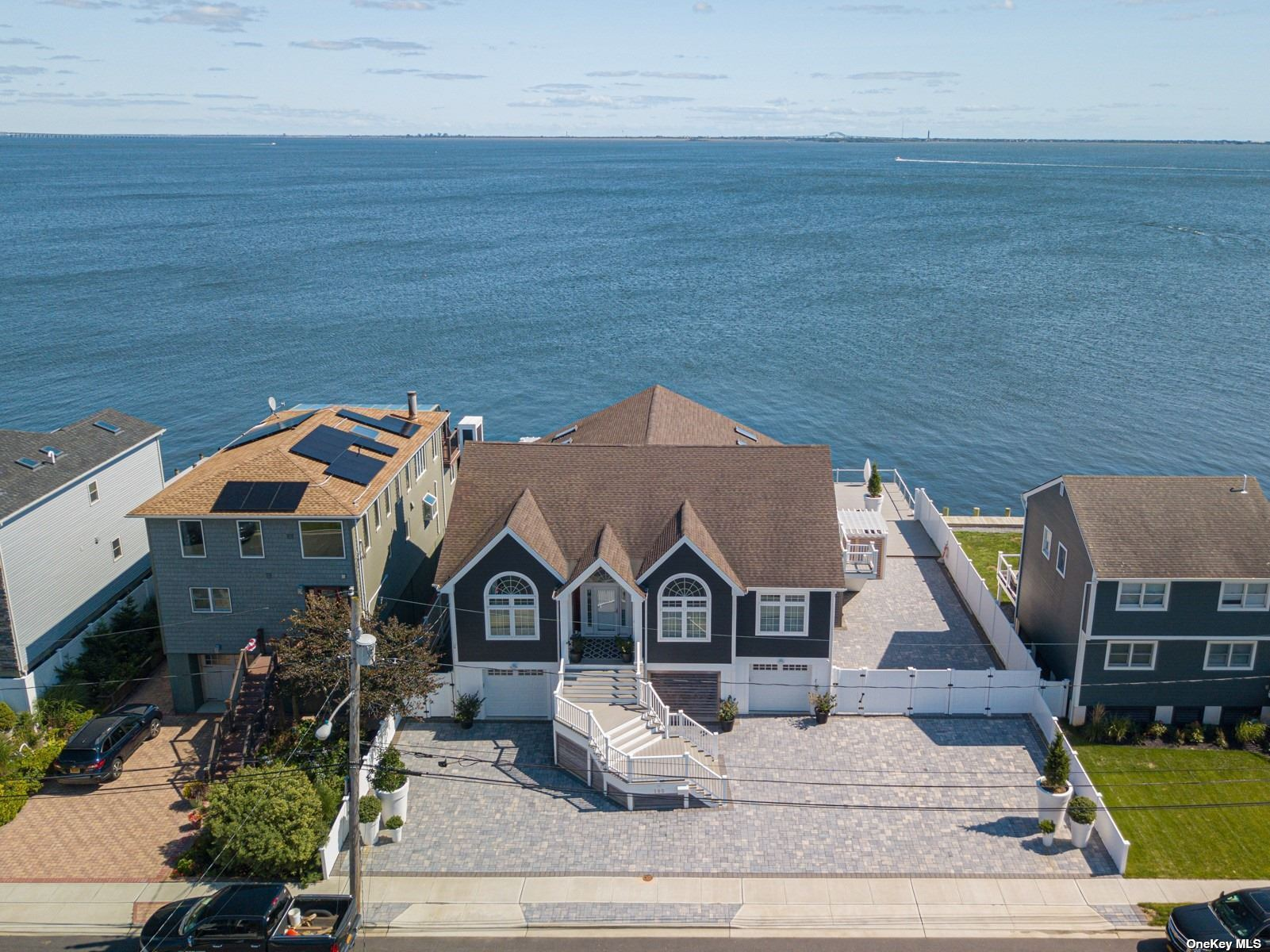Astonishing Views And Magnificent Details In This Unique Waterfront Estate. Facing The Great South Bay, This Sundrenched Home Offers From The Welcoming Foyer To The Great Living And Dining Room In the Back, The Mesmerizing Views Of The Ocean Through The Amazing Windows And Sliding Doors, Open Design Gourmet White Kitchen, 18 Ft High Cathedral Ceilings With 4 Skylights, 4 Bedrooms, 2.5 Baths, Radiant Tiles, CAC, 200 Amp Elect, 35x16 Sq. Ft. Salted Water Inground Pool Surrounded By 2,080 Sq. Ft. Gorgeous Trex Deck, Hot Tub, Terrace With Pergola And Balconies, 3 Car Garage With An Electrical Charger, 5-Car Stone Pavers Driveway, Enormous Walk Out Attic, Huge Basement,  All Fenced. Close To Train (5 Min Drive), Shop  & Restaurants. Community Private Beaches And Parks.