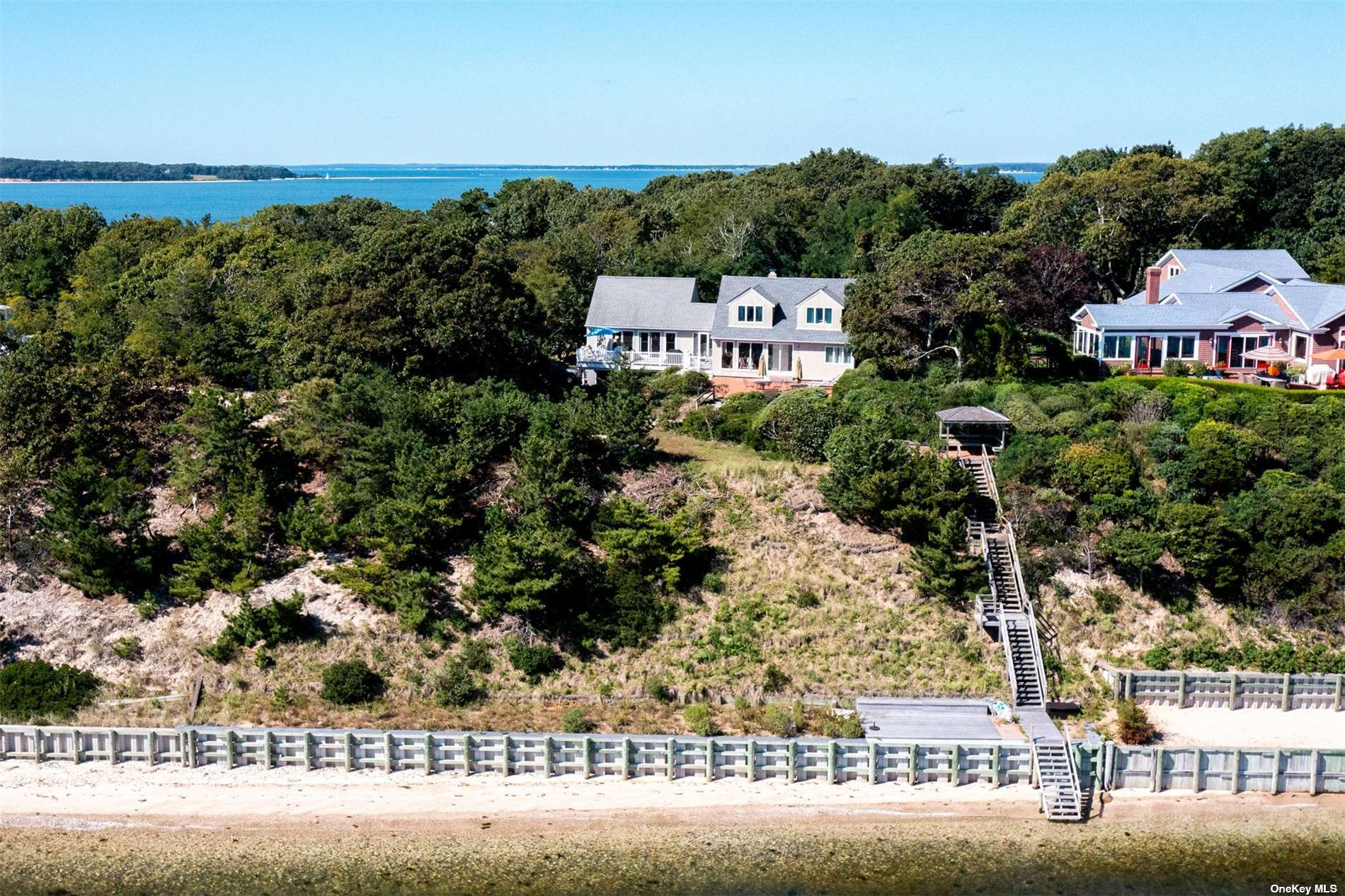 Sunrise and Sunsets. At the end of the Nassau Point Penninsula high up in the trees surrounded by water sit this lovely private beach house with forever views across Little Peconic Bay to Southhampton and Jessups neck. Big spacious open floor plan, enclosed by a wall of sliders to acccess the brick patio, seaside gazebo, 140' of new bulkheading with a sun platform, revegetated bluff, and a beautiful sandy beach.
