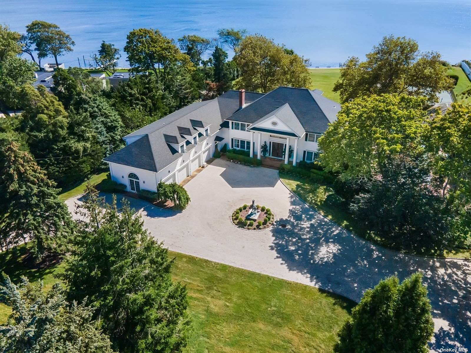 Sweeping waterfront views on Bellport Bay Cove.  The property features 2.48 acres with 200 ft. of bulkhead and dock.   Enter the grand marble foyer with oversized doors and immediate views of Great South Bay, as the foyer runs the entire width of this 3 Story Colonial Estate.   The main floor consists of a large living room with fireplace, a family room with fireplace and wet bar for entertaining, formal dining room, country kitchen with granite counters, custom cabinetry, island with seating, large area for kitchen table, and butlers pantry.  There is a wood paneled office lined with book shelves overlooking heated gunite pool, 2 half baths, and mudroom laundry area.  Upstairs are a master en suite with 2 tremendous walk in closets and his &  her baths.  A second en suite bedroom, 3 guest bedrms, full bath, half bath and gym area.  The third floor has game room with half bath.  4 car garage, tennis courts, putting green, gunite pool with pool house, and elevator.  Too much to list!!