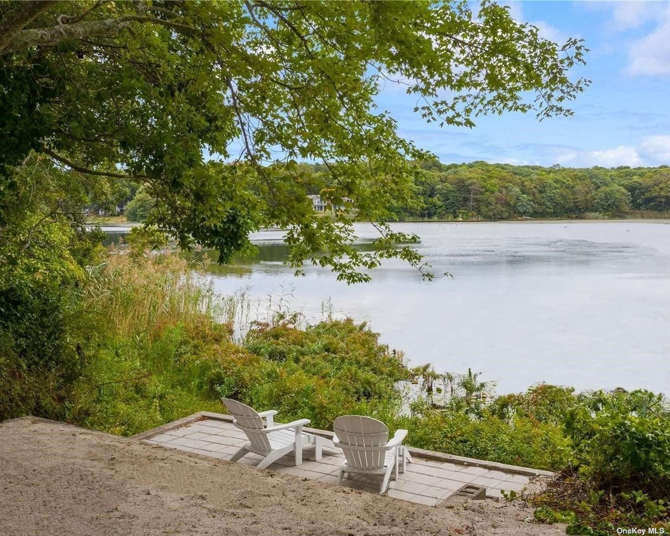 """New to the Market!!! Quintessential North Fork Waterfront Beach Cottage! Wiggle your toes in the sand from your own back yard. Enjoy the peacefulness of Great Pond. And then put on your flip flops, grab a towel, and be at the beach- just a short walk down the road.  The home is move-in, completely updated and waiting for you.  Open plan with beautiful kitchen, living and dining, two bedrooms, full bath, half bath and outdoor shower. Light and bright, everything is pristine. Property sold """"as is"""". Own this get-away cottage and enjoy all four seasons- it's time!"""