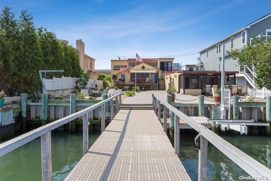 Bayfront Beauty! 60 Feet of Direct WaterFront w/ Endless Views.40 Foot Pier w/ Dining Area,Lower Boat Access & Jet Ski Lift.Updated Bulkhead. Yard w/ Upper and Lower Decking, Pavers, Grassy Area w/ Vegetable Garden. Custom BBQ w/ Natural Gas, Fire pit. Sep Boathouse w/ Full Bath, Wet Bar & Screened in Front Den. Solar Panels, 2 Tesla Car Chargers, 2 Car Garage & Extra Long Driveway. Beautiful Breezeway Entry. Open Living Space w/ Cathedral Ceilings Leads out to Back Yard Upper Terrace w/ Awning. Water Views from Every Window. Main Level Open Kitchen w/ Dacor Stove and Double Oven. Formal Dining Area. Separate Den/TV Room. 2 Beds & Full Bath Main Level. Powder Room. Laundry Room. Ductless Air Conditioning Systems Throughout. 4 Zone Heating w/ Cast Iron Baseboards. Spectacular Master EnSuite on Top Level Boasts Radiant Heat, Large Sitting Area,Office Nook,Walk-in Closet,Wide Open Bay and Sunset Views w/NYC Skyline Backdrop. Finished Basement. See Virtual Tour for full walk-thru video.
