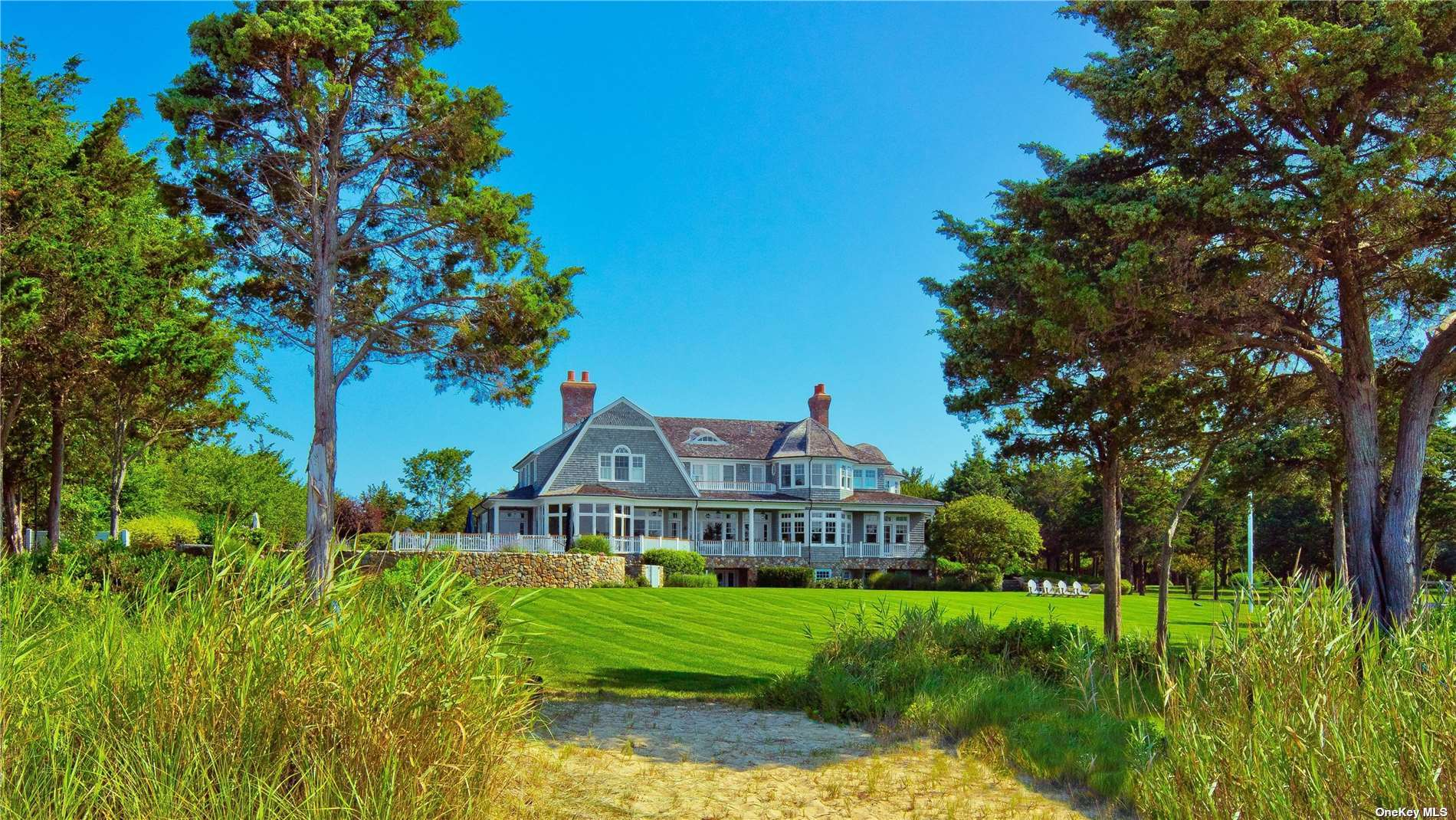 """""""The Esplanade"""", A private estate surrounded by water & preserved land with 170' of sandy beach, fronting Peconic Bay. Nantucket style 7000sf home, crafted with crown moldings, NF Stone, cedar shake, and marble. Cooks are delighted by the two tone Clive Christian Kitchen outfitted with La Cornue Gas Stove, Sub Zero & Miele appliances. The kitchen blends into the dining/living room enclosed by glass overlooking sprawling lawn and sea. A well designed interior encompasses a Mahogany Library, Sunroom, 2 office, 4 fireplaces, a back staircase, coffered ceilings, and window seats, add warmth & timeless elegance. A generous Master plus 4 ensuite bedrooms are classically designed and finished with waterworks faucets and LeFroy-Brooks shower systems. The Home, outdoor kitchen, heated salt water pool, and Jacuzzi, are sited at the perfect elevation to capture views of the sandy beach and Peconic Bay."""