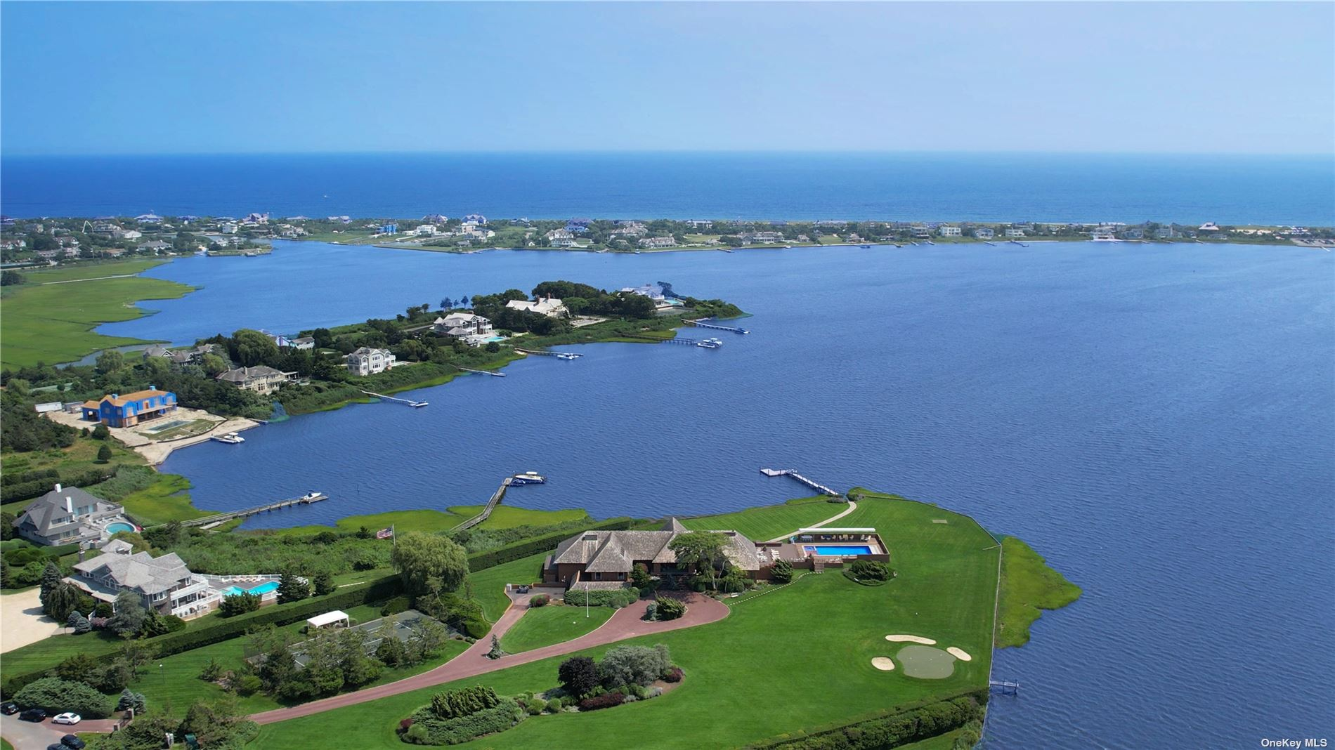 An Impressive And Premier Waterfront Estate Designed By Renowned Architect, Norman Jaffe, In Quogue On The Desirable Quantuck Bay. This Exquisite Estate Spanning Over 3 Acres and 420 +/- Feet Of Bulkheading Includes Two Docks, Southwest Views From Bay To Ocean, And The Most Spectacular Sunsets, Is Not To Be Missed. With 7,850 +/- sqft., Over 8,000 sqft. Of Outdoor Decking, A 20 x 50 Ft Pool, Spa & Sundeck, Tennis Court, Professional Putting Green, 100 Ft Stationary Pier With 30 Ft Floating Dock, There Is No Need To Look Farther East When You Can Own Your Own Hamptons Waterfront Haven Right In Quogue!  Also, Available As A Package With A Buildable Vacant Lot Of +/-2.7 Acres At 2 Seascape Lane For $17,999,999.