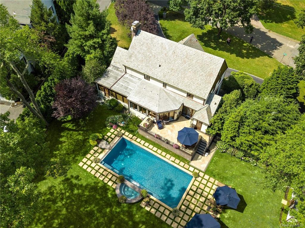 This Chic Stone Front Tudor, with a circular driveway, less than 35 mins from NYC, is the perfect place for you to completely de-stress & unwind. Don   t miss any time that can be spent in your backyard oasis. Turn your Zoom screen to    no-video    & just walk outside from your first floor home office to enjoy a dip in your own Saline pool complete with waterfall, spa tub & free form rock diving board. Grill meals on the Lynx BBQ, which is part of the entertainment center on the gracious stone patio. A large family room & additional playroom are just steps away from the beautiful modern kitchen with its leathered marble island & over-sized dining area. In winter months, relax by the wood burning fireplace in the inviting living room and enjoy holiday gatherings in the spacious formal dining room. The master bedroom with en suite bath, 3 spacious bedrooms & recently renovated luxury hall bath are all on the same level (Sq ft includes finished basement). Enjoy Scarsdale Schools & Recreation.