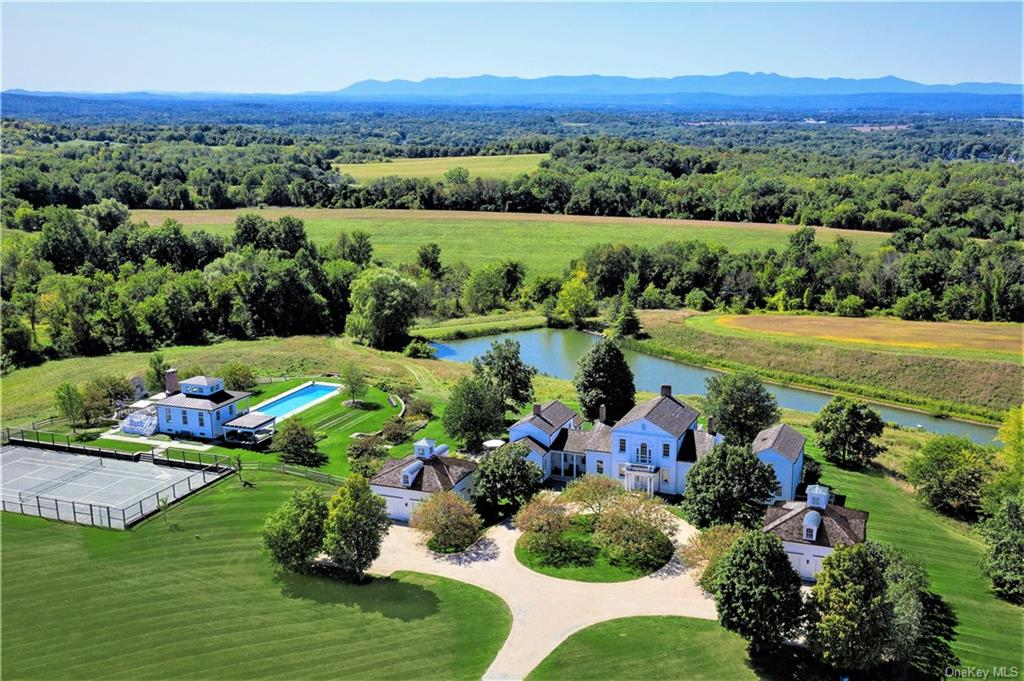Privately situated up a long winding drive through the apple orchard you will find this exquisitely crafted estate on 100 serene Old Chatham acres. The hilltop setting was crafted to take full advantage of 360 degree panoramic views in every direction, from the breathtaking sunset views over the Catskills to the sunrise over the Berkshires. The pastoral setting includes a large pond that winds along the hillside below the home, mature trees and extensive walking trails. The estate contains a manor house, luxurious pool house, 70    heated gunite pool with separate spa, tennis court and two lofty studios with full baths and mini kitchens above two car garages. Designed by the area   s leading architect and completed by master craftsmen, every room embraces a fresh classic style with exquisite attention to detail: custom millwork, elegant fittings, interior shutters, and 11-25    ceilings creating an airy sense of comfort with the features most desired for modern family life and entertaining.