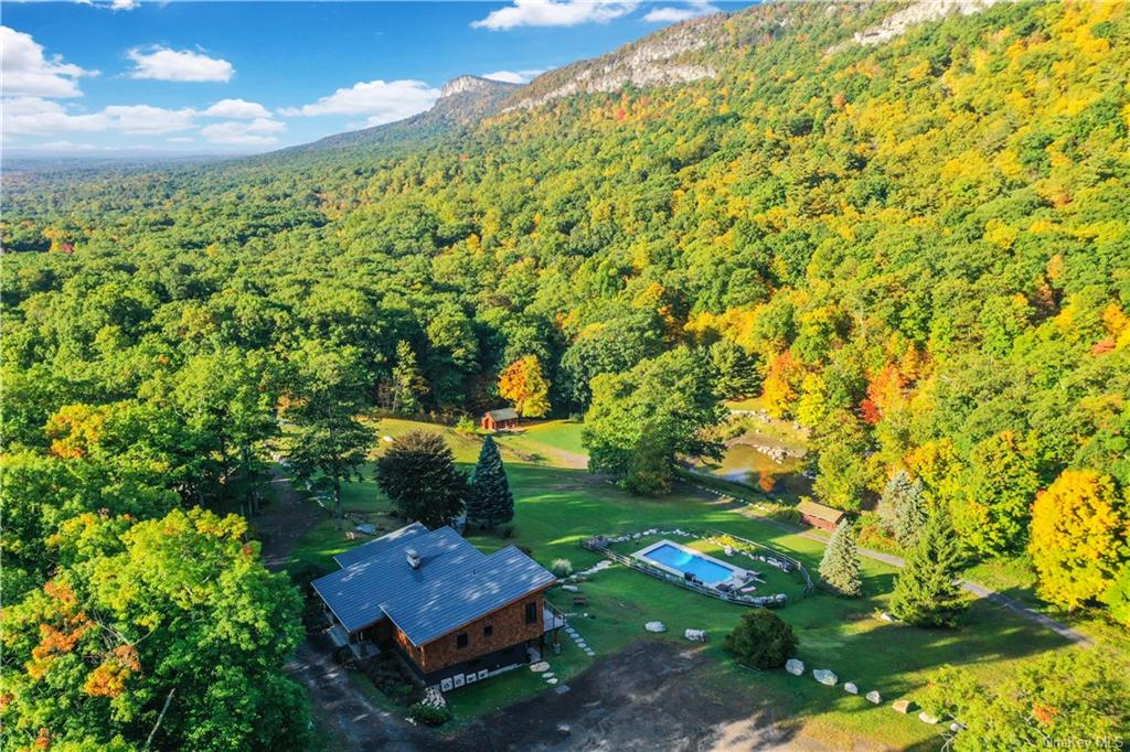 MOUNTAINSIDE RETREAT offering priceless views of the Shawangunk Ridge. The view is your playground! It   s Magical, the seeminglyimpossible dream is realized in this Contemporary Arts & Crafts estate perched at the Gateway to the Shawangunks occupying a perfectvantage point for unequaled panoramic views. Unique opportunity to own a part of the Shawangunk Ridge with direct access to the worldrenowned Trapps climbing cliffs and the 7000 acres of Mohonk Preserve with 70 miles of historic carriage roads and trails. One of the foremostcraftsmen in the area created his Crown Jewel with expansive mahogany decking overlooking your own private world with inground pool andpond. When you enter the home, you are greeted with soaring ceilings and walls of glass offering a breathtaking experience at all times of day.Great- room with cedar ceilings features Chef   s Kitchen with expansive stone counters, farm sink and island. No attention to detail has beenspared: radiant heat on ground floor, wide board white oak floors with water-based sealer for a natural sheen, 5 new energy efficient AC heatpumps, foam insulation, two stone fireplaces, top of the line Marvin Ultimate windows, standing seam metal roof, electric power shades, customwalnut and cherry vanities, slate floors and custom trim in all baths. Master suite features floor to ceiling glass with views to Millbrook Mountain,generous walk-in closet, luxurious master bath offering three shower heads and views of cliffs from within shower. Bedroom two has its ownprivate bath. Lower level offers den, full bath, additional bedroom, family room with fireplace, office and laundry room. Amazing tranquil retreat,truly a gem that affords a rare opportunity to own your own piece of the Gunks. Conveniently located just minutes from the happening town ofNew Paltz and Gardiner. Easy NYC commute: 10 Minutes to the I-87 and express NYC bus.