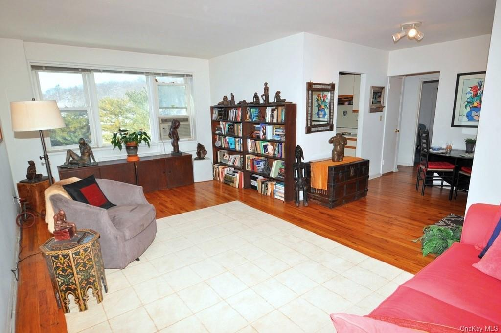 Sunny living area has refinished hardwood floors, opens to the dining foyer and South West exposures.