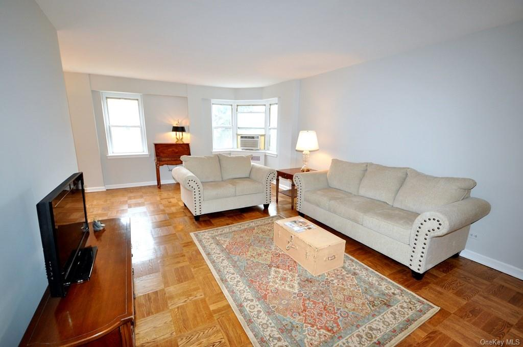 Large living room with refinished parquet floors opens to the
