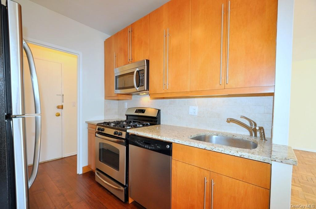 Updated Kitchen with Granite Counters, custom cabinets and stainless steel appliances including a dishwasher, microwave, range and refrigerator.