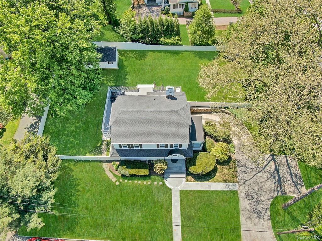 """Perfectly nestled on .36 acres in the coveted Greenacres section of Scarsdale, this renovated colonial has tremendous expansion possibilities.  Surrounded by larger homes, this corner lot has the possibility to expand and create a dream home similar to the residences down the street.  The """"park like"""" backyard is open and flat, surrounded by a new white fence securing a dog or child.  The large deck is ready for BBQ's and summer fun!  Inside this classic colonial is an updated kitchen with new appliances and two new bathrooms.  The living room boasts a wood burning fireplace and splits out to a sunroom and family room.  The primary bedroom has architectural plans for an en-suite bath and down the hall are two guest beds and hall bath.  Basement is updated with new bathroom, laundry & utility closet.  Garage opens to a large wrap-around driveway leading to the new path and front stairs. New 12x20 storage shed.  Walk to elementary school.  Property survey & architectural plans available."""
