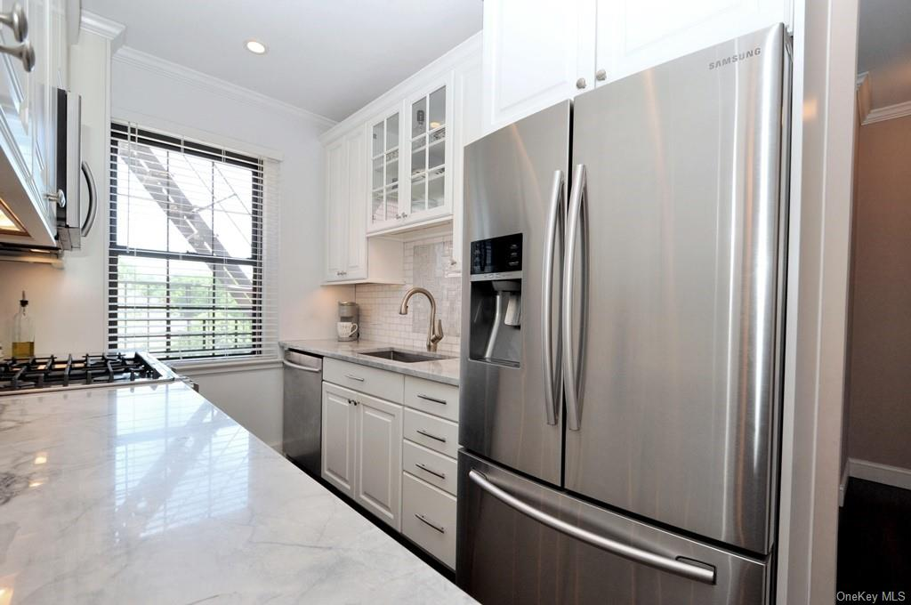 Fully Renovated kitchen with quartz counters, subway tile back splash, custom cabinets, and stainless steel appliances including a dishwasher, slide in range, microwave and French door refrigerator.