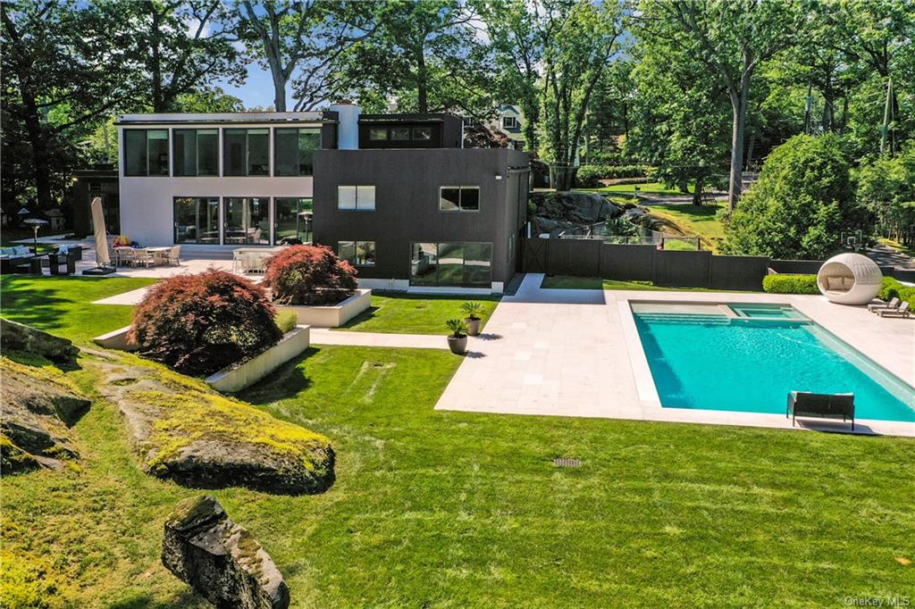 SoHo meets Scarsdale! Contemporary living at its finest with privacy in Murdock Woods. Almost one acre of professionally landscaped property with new 25 x 45 foot gunite pool, spa, electric cover, patio. Open concept living room, dining room, family room, kitchen with professional stainless steel appliances. Wall to ceiling windows overlooking the exquisite backyard. Sliders to the newly renovated patio with outdoor kitchen, make for easy entertaining. Second level features two bedrooms with renovated hall bath, third bedroom with renovated en-suite bath. Conveniently located second floor laundry room with new washer/ dryer. Spacious master suite on the third level overlooking entire property. His/Hers walk-in cedar closets, updated master bath en-suite, adjacent work out area and home office space, complete the room. Lower level playroom with sliders to the backyard, den/bedroom, renovated bath and entry to two car garage. Full house generator. New hot water heater. Pool shed. Country club living in your backyard.