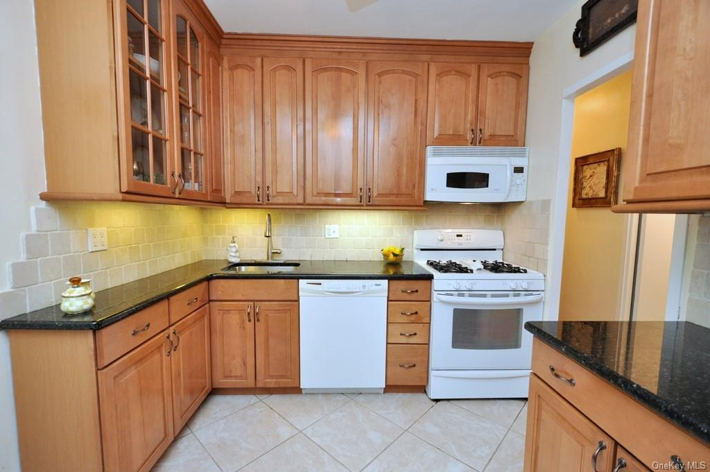 Renovated Eat-in-Kitchen with granite counters, cherry cabinets and appliances include a dishwasher, microwave, range and refrigerator.