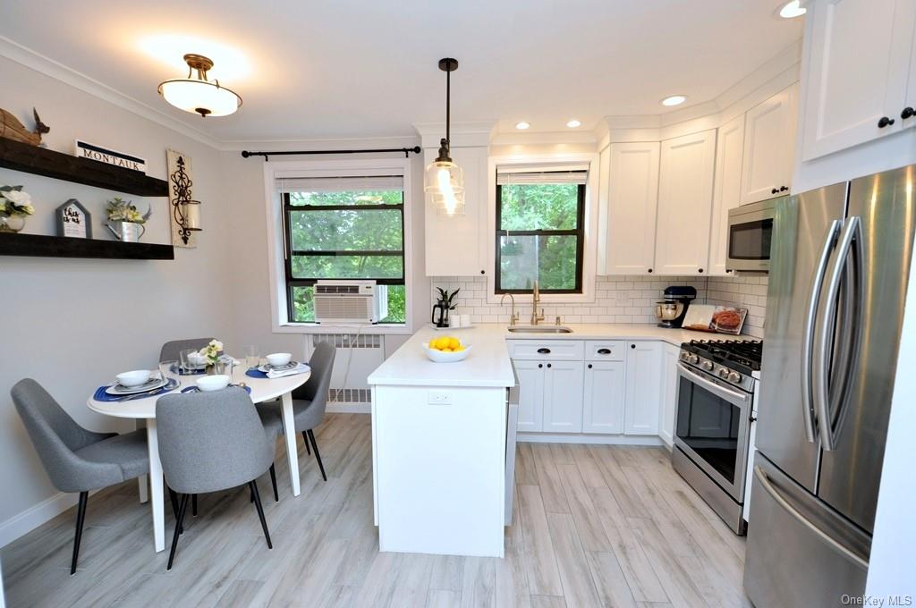 Redesigned eat-in-kitchen has quartz counters, stainless steel appliances, custom cabinets, new floor, crown molding and center peninsula.