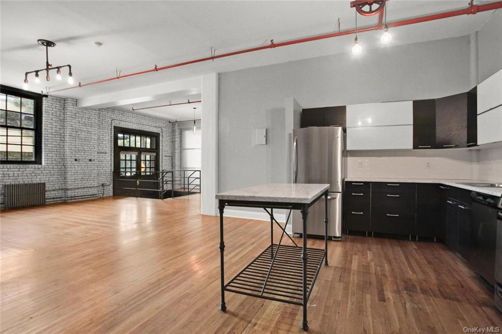 Rare loft condo unit in The Knickerbocker Lofts in New Rochelle!  Enjoy the beautifully renovated SOHO-style industrial loft with 1200+ sqft, original wood floors throughout.  Whether you work from home (needing space for Zoom calls or making art) or commute to NYC (close to MetroNorth!), this loft is it!  High ceiling, modern eat-in kitchen, living room with exposed bricks and custom sliding doors for bedroom and walk-in closet.  Commuter's delight!  Only 0.5 miles easy walk to New Rochelle MTA station.  Enjoy all that downtown New Rochelle has to offer.  Building has fitness center, club room with fireplace and panoramic rooftop deck.  Pet-friendly building!