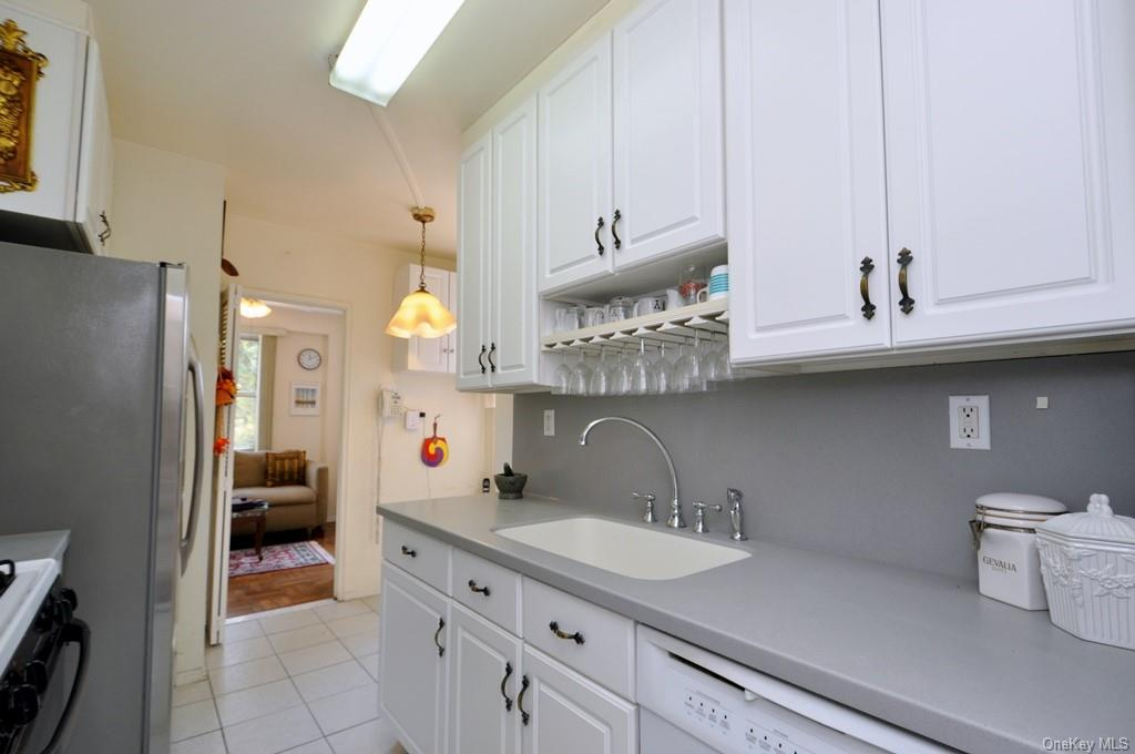 Updated eat-in-kitchen with custom cabinets, Corian Conters and backsplash, appliances include a dishwasher, microwave, range and refrigerator.