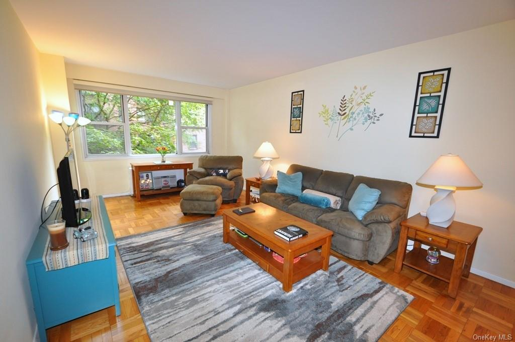 Large living room has picture window, refinished parquet floors and is 20'-0